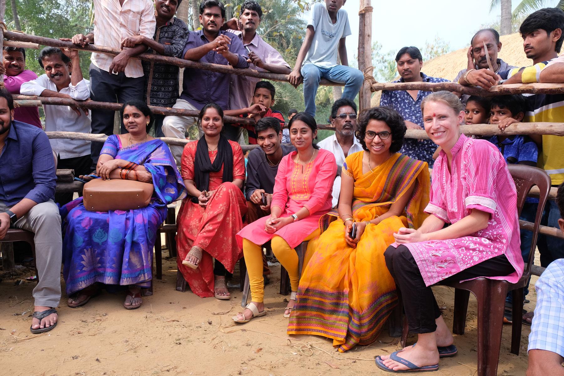 Leo sitzt neben indischen Frauen in einer Arena für Hahnenkämpfe.