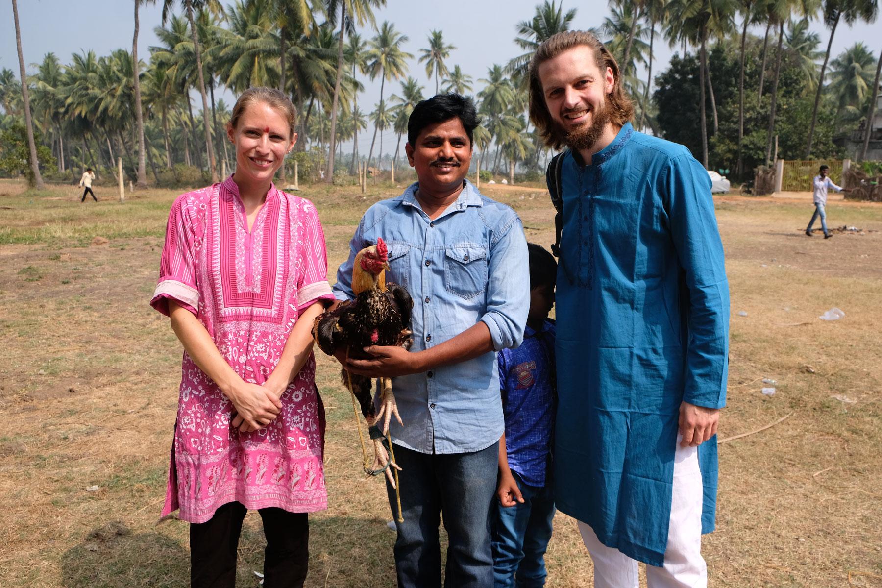 Leo und Sebastian neben einem indischen Mann in Bhimavaram, der einen Kampfhahn auf dem Arm hält.