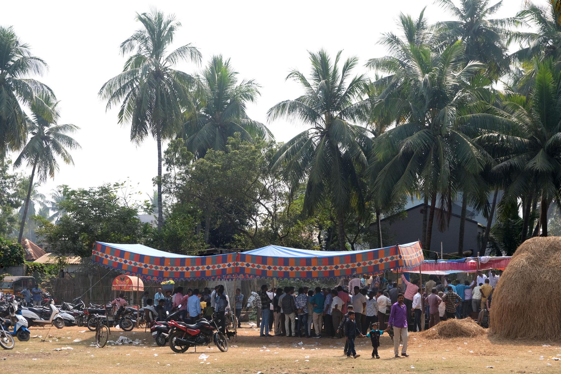 Menschen stehen unter einem bunten Plane und feiern das Sankranthi Festival.