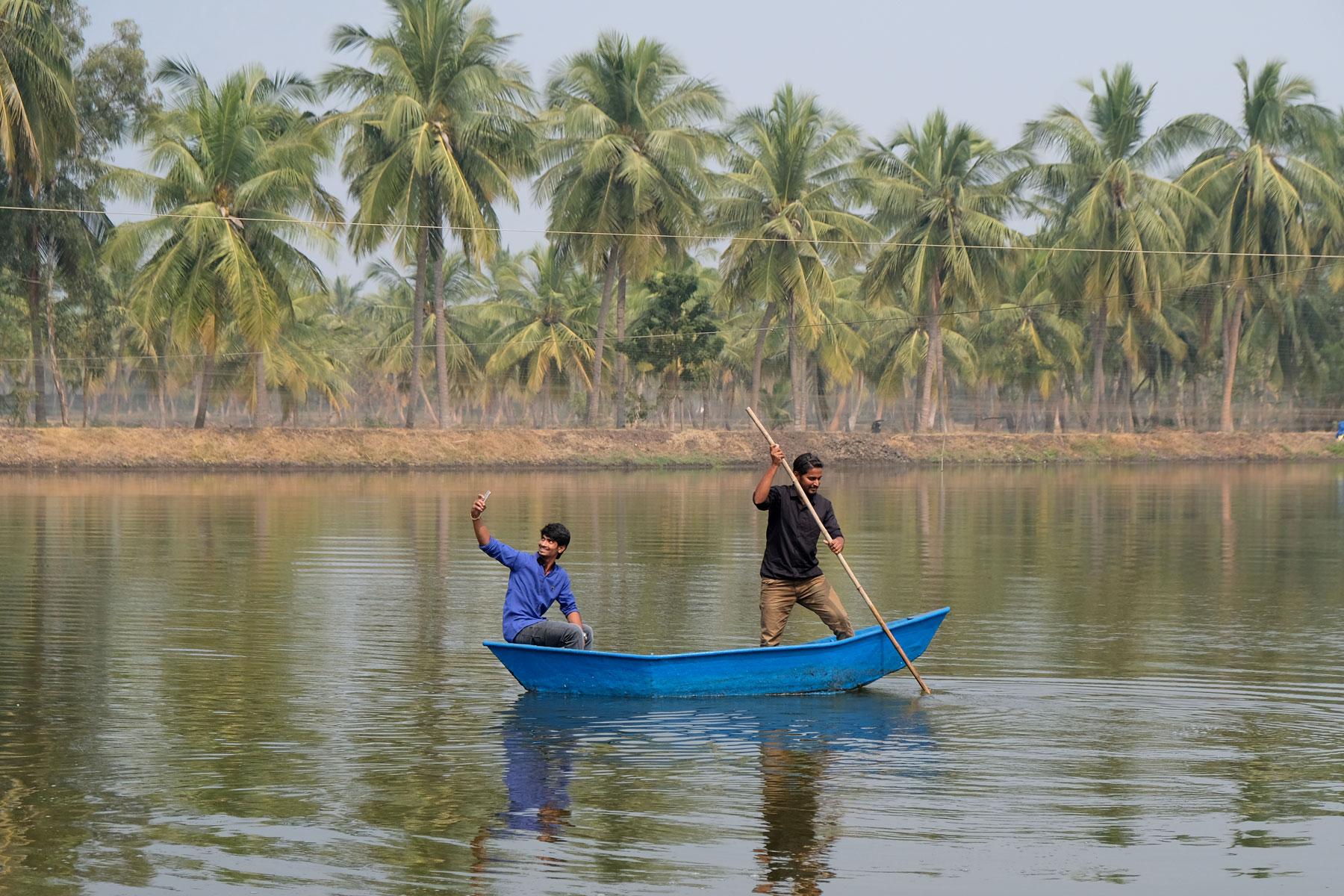 Zwei indische Männer in einem kleinen Boot auf einem See.