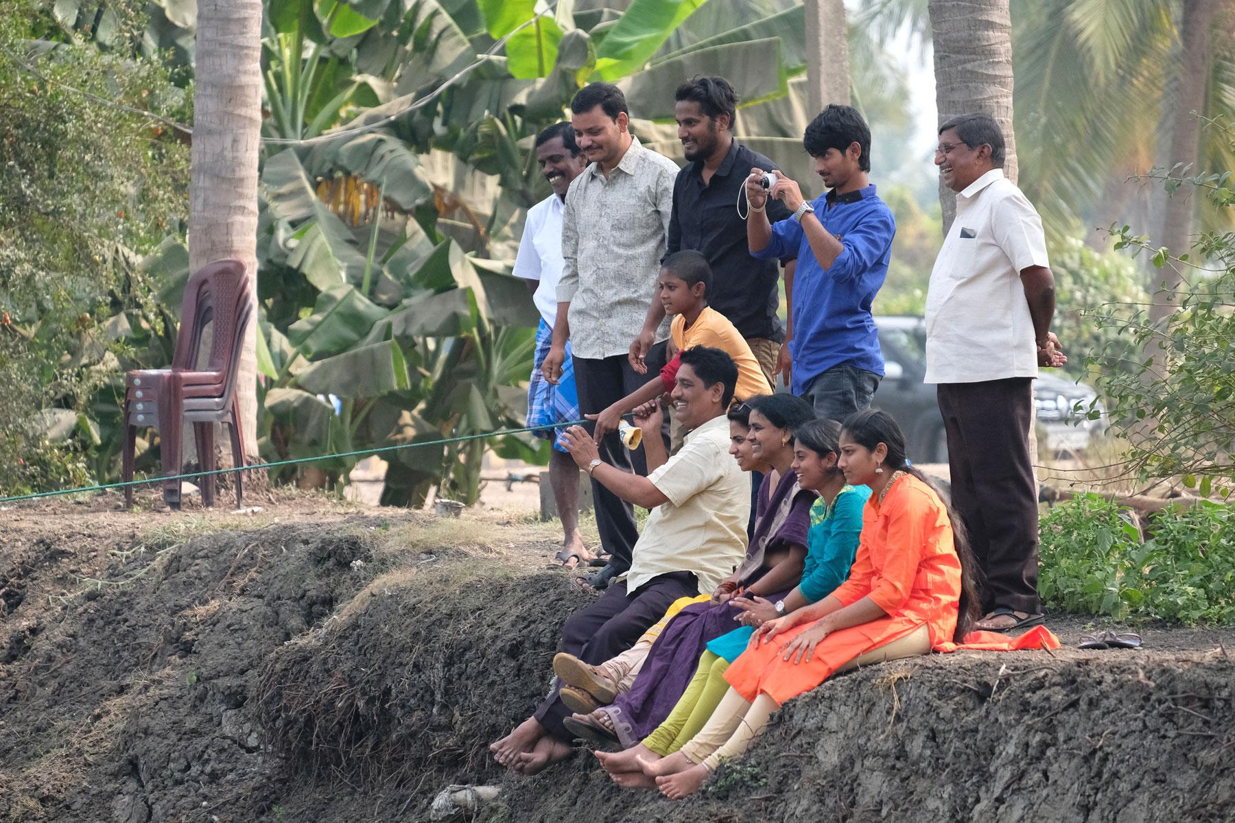 Indische Menschen sitzen am Ufer eines Sees.