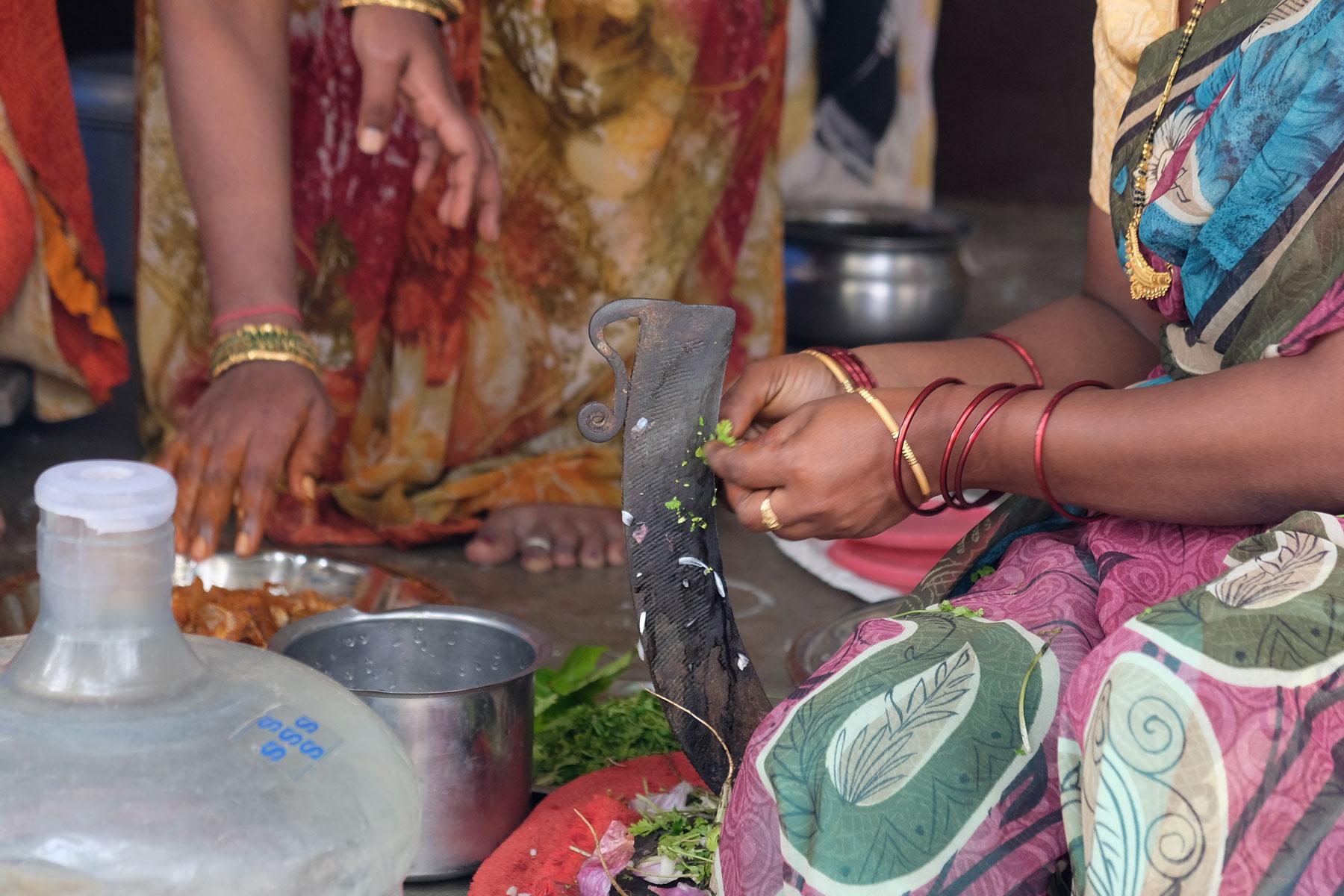 Eine indische Frau schneidet Kräuter an einem Messer.