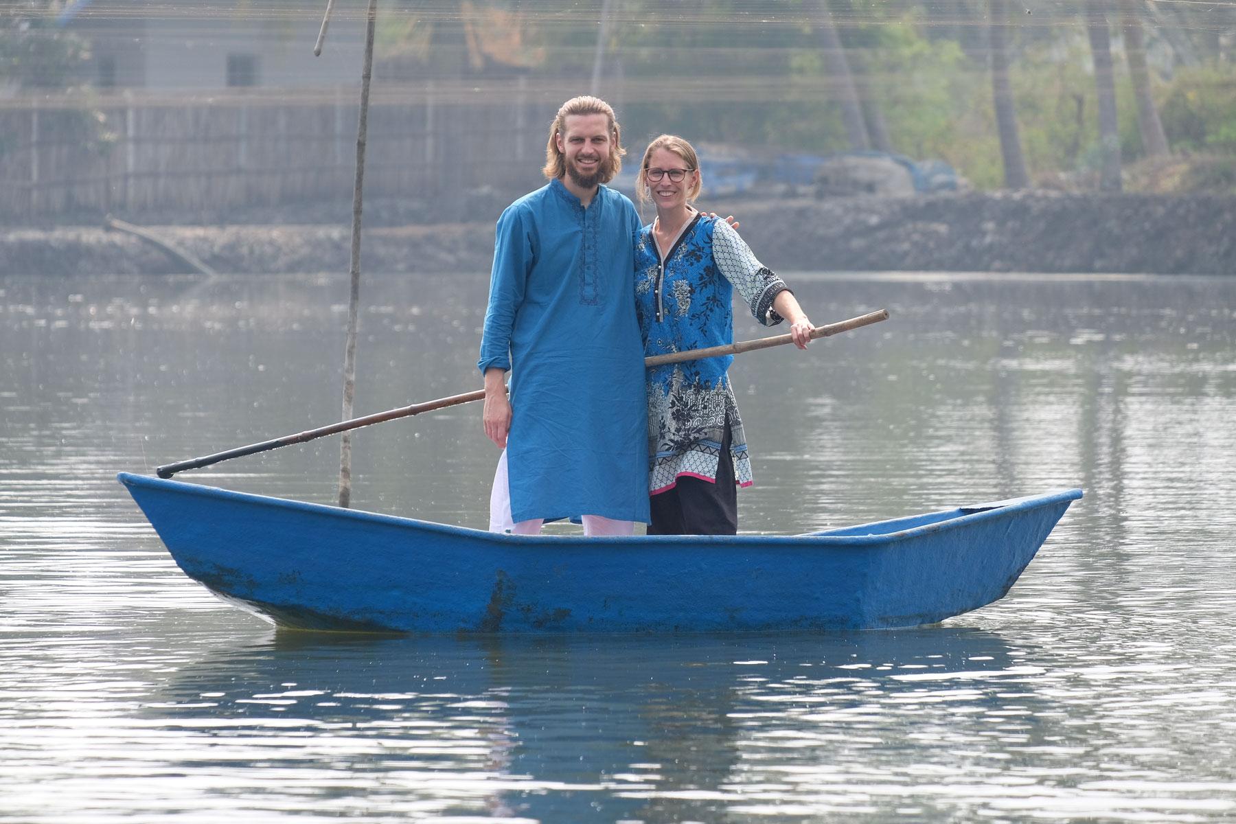 Sebastian und Leo stehen in einem kleinen Boot auf einem See und halten einen langen Stock in der Hand.