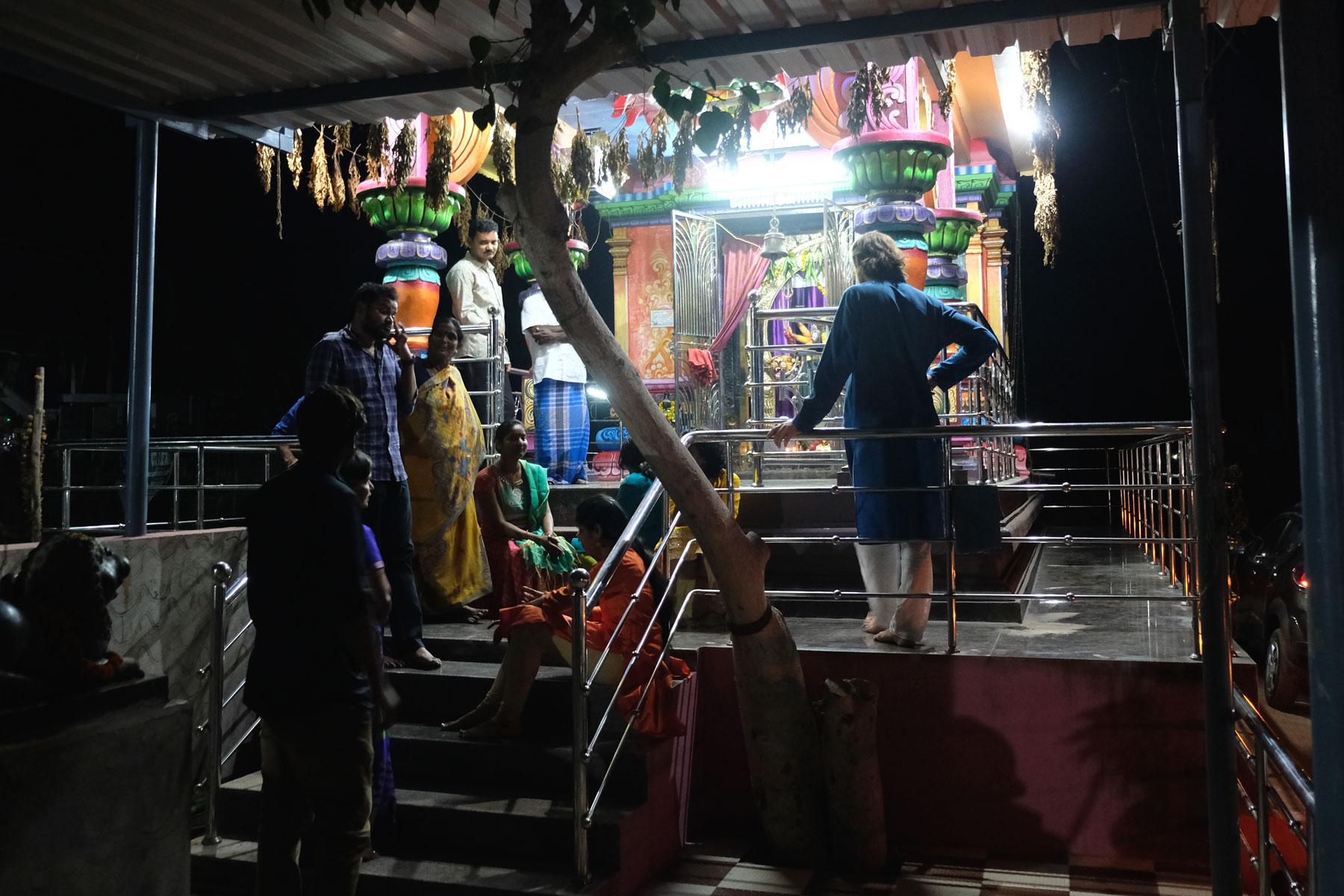 Menschen stehen nachts vor einem indischen Tempel.