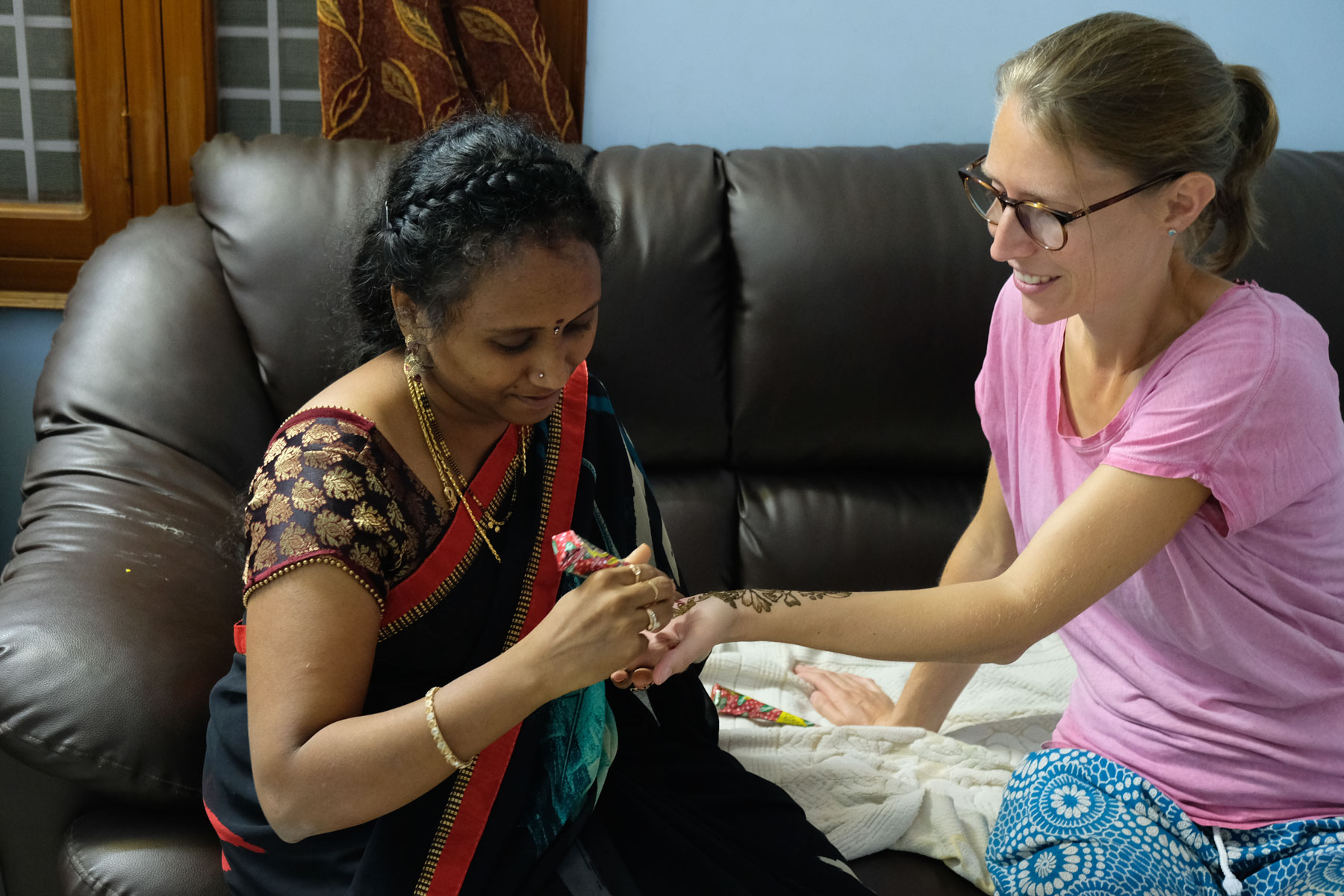 Eine indische Frau malt Leo ein Hennatattoo auf den Arm.