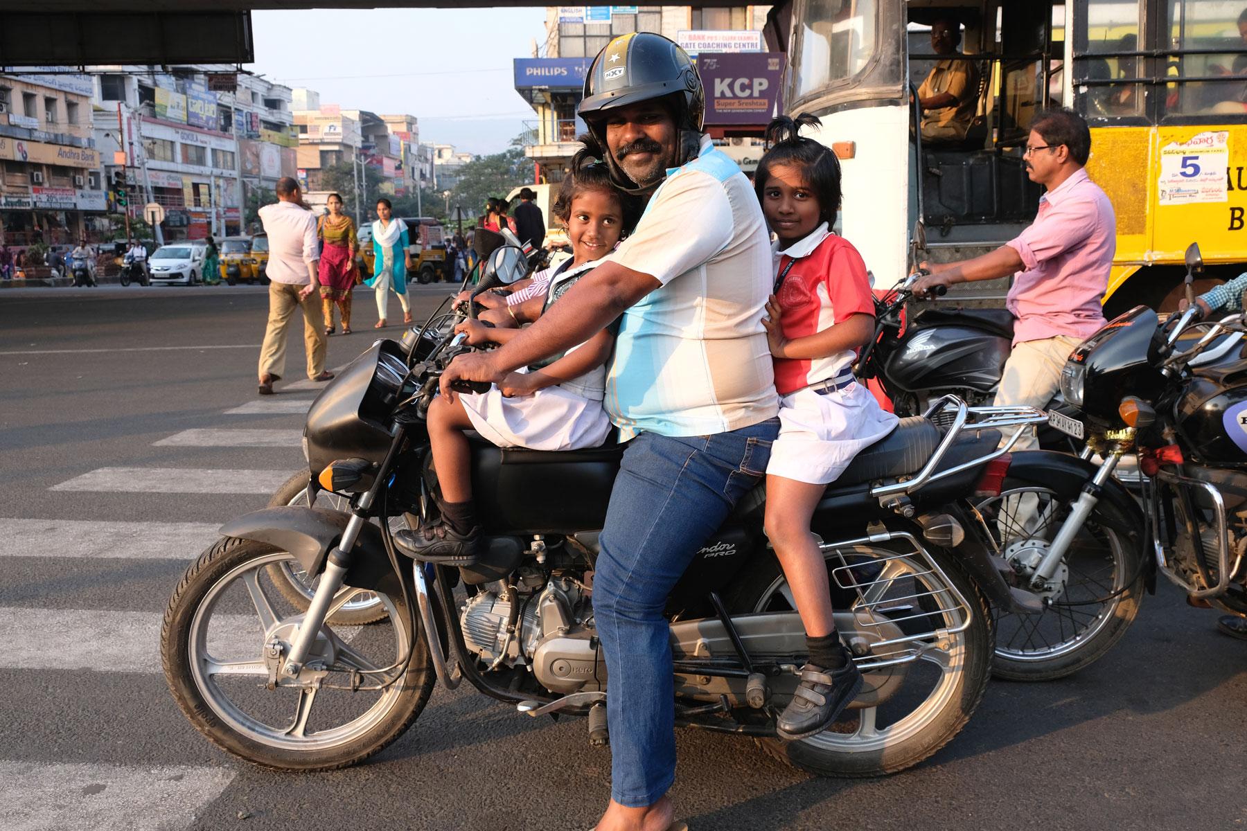 Ein indischer Mann und zwei Mädchen sitzen in Visakhapatnam auf einem Motorrad.