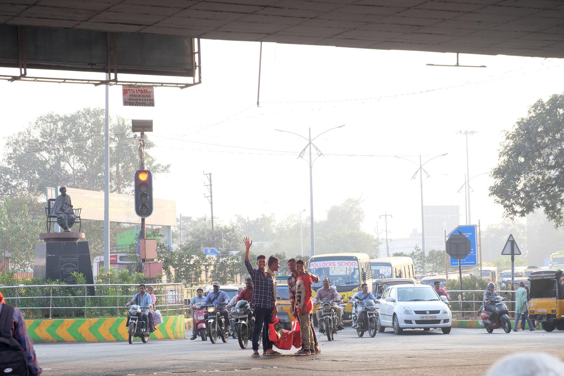 Winkende Männer auf einer Straßenkreuzung in Visakhapatnam.