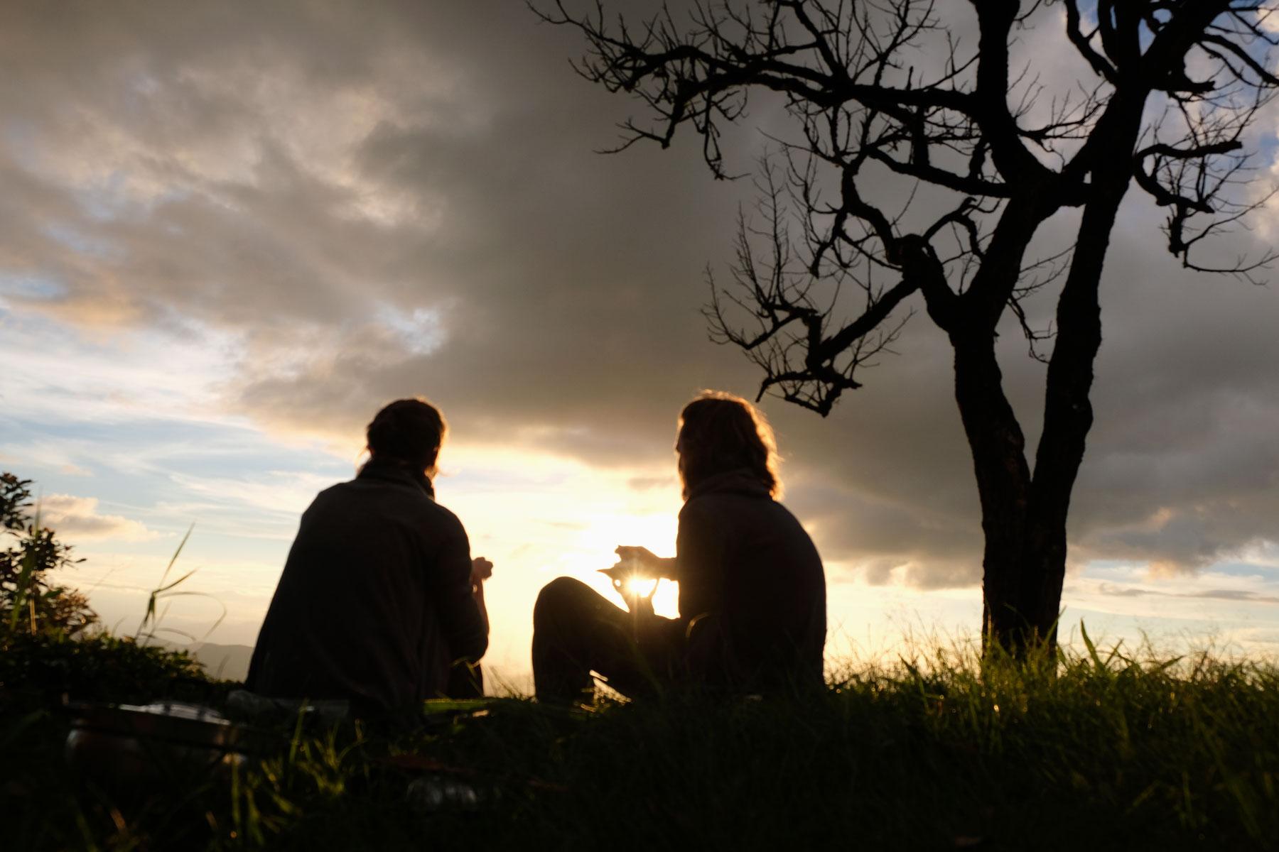 Leo uns Sebastian sitzen neben einem Baum in der Abendsonne.