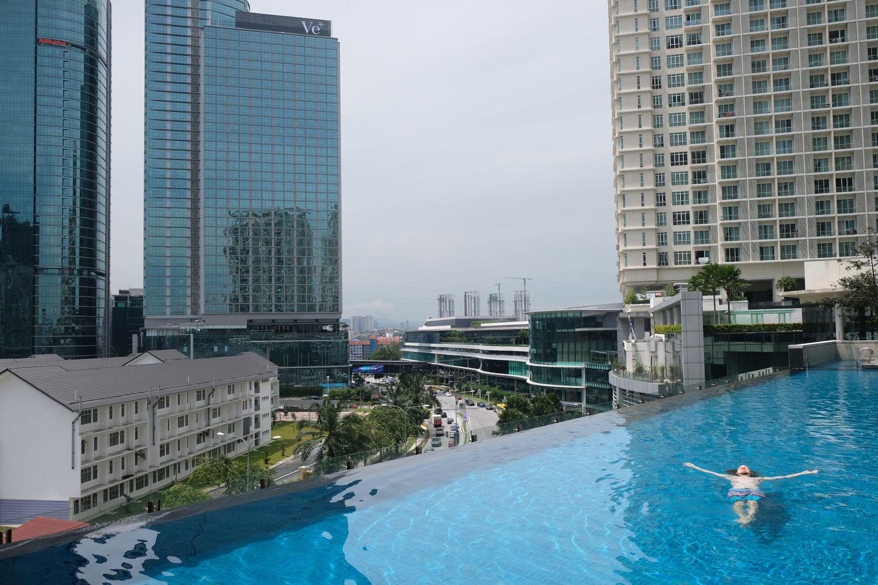 Sebastian schwimmt in einem Infinity Pool in Kuala Lumpur.