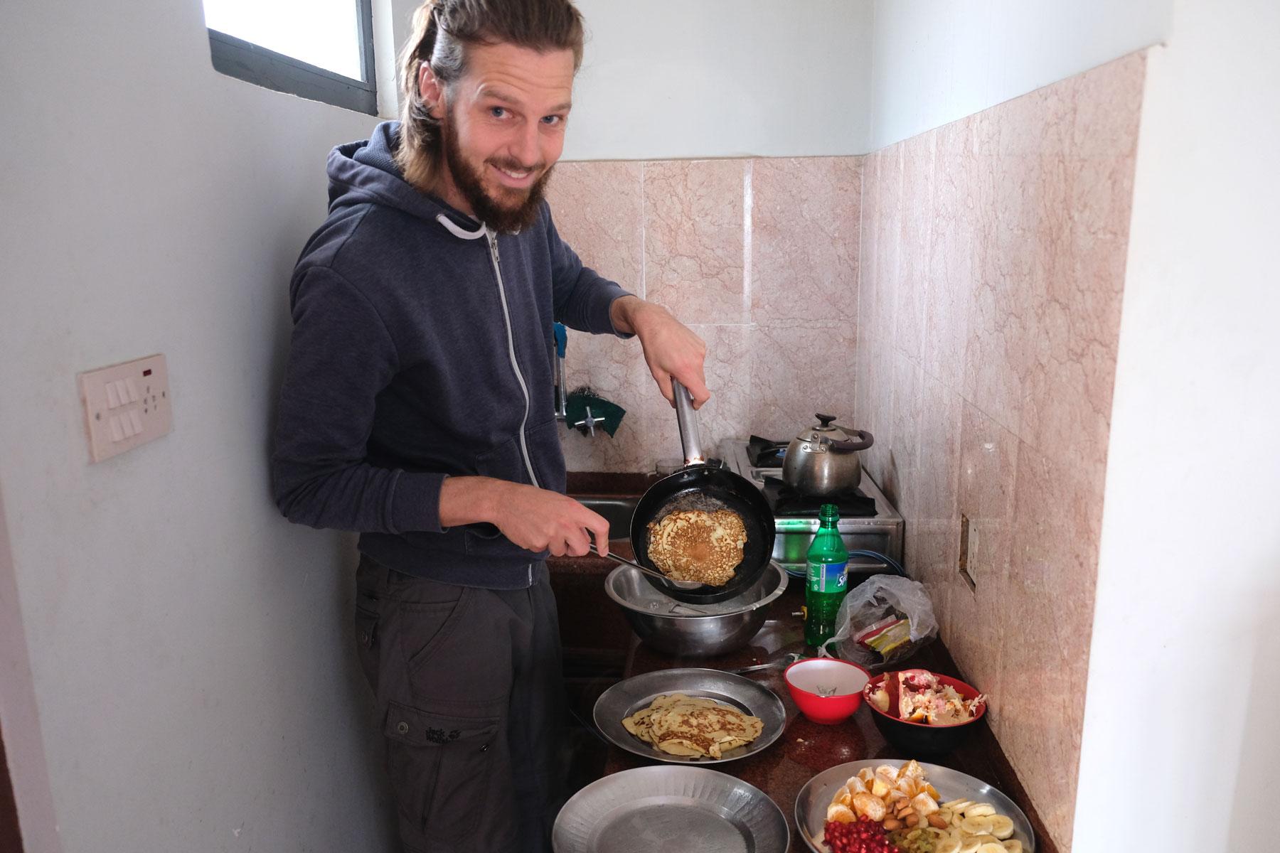 Sebastian kocht Pfannkuchen in einer kleinen Küche.