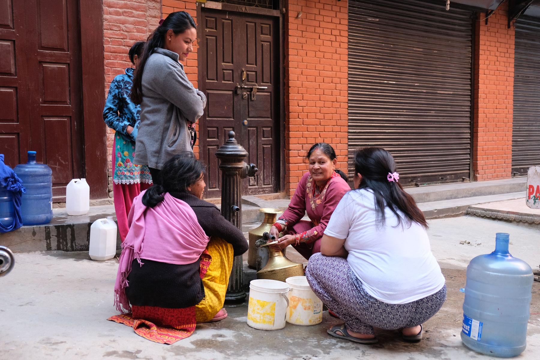 Nepalesische Frauen füllen in Kathmandu Wasser aus einem Brunnen in Kanister.