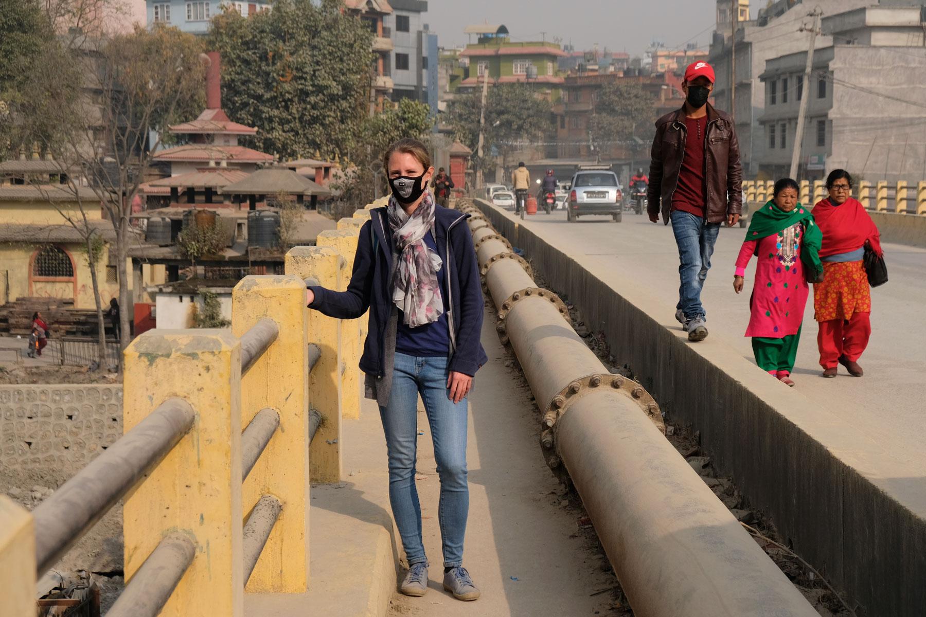 Leo steht auf einer Brücke in Kathmandu und trägt eine Atemschutzmaske.