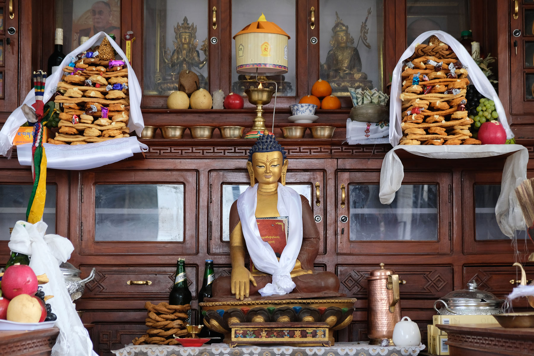 Buddhistischer Altar mit einer Buddha-Statue und Opfergaben.