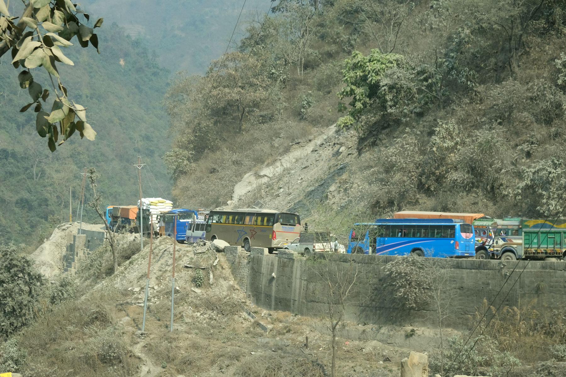 Busse und Lastwagen stehen im Stau auf einer Straße in Nepal.