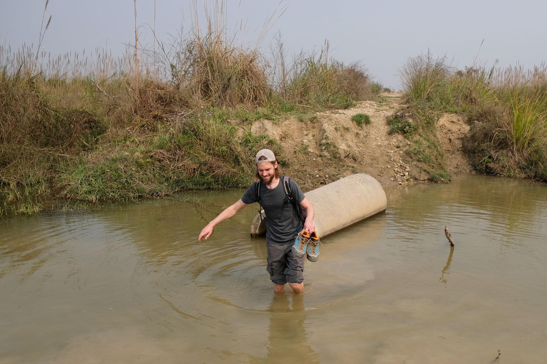 Sebastian watet durch einen Bach im Chitwan Nationalpark.
