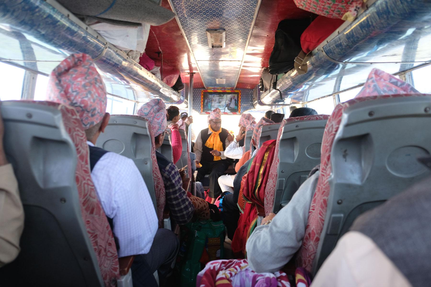 Nepalesische Pilger mit rosafarbenene Hüten in einem Bus.