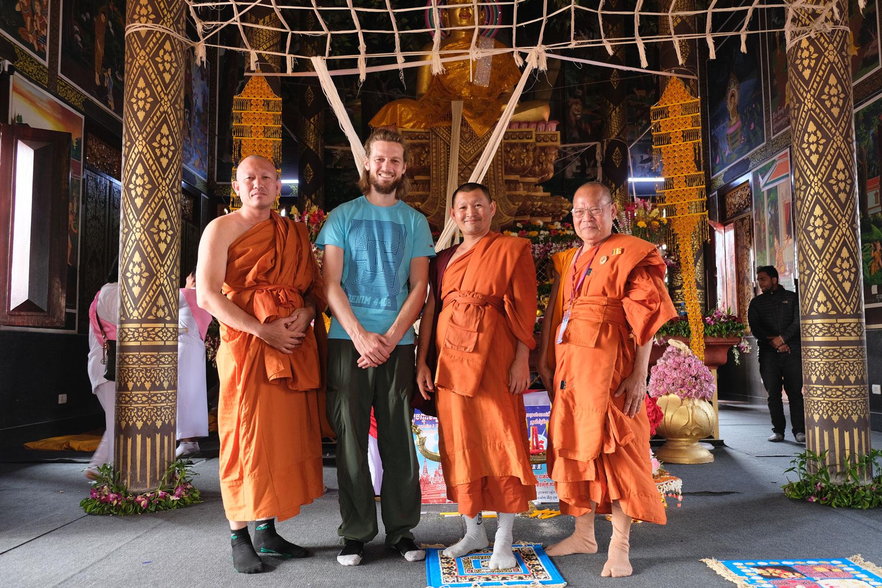 Sebastian neben drei buddhistischen Mönchen im kambodschanischen Tempel in Lumbini.