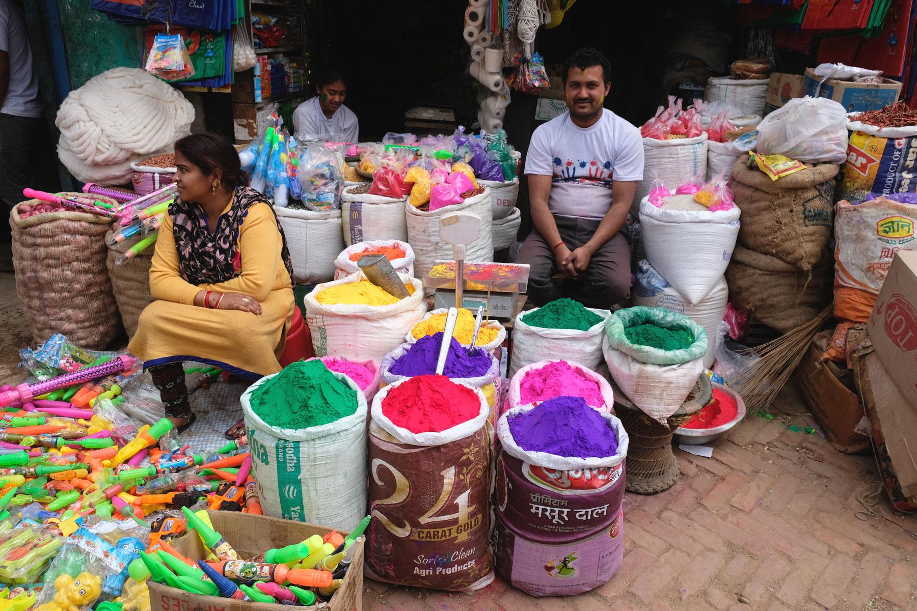Zwei Verkäufer in Tansen mit Säcken voll buntem Farbpulver für das Holi-Fest.