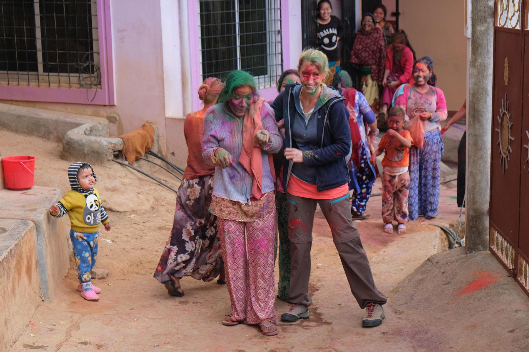 Leo und eine nepalesische Frau mit bunt angemalten Gesichtern beim Holi-Fest in Tansen.