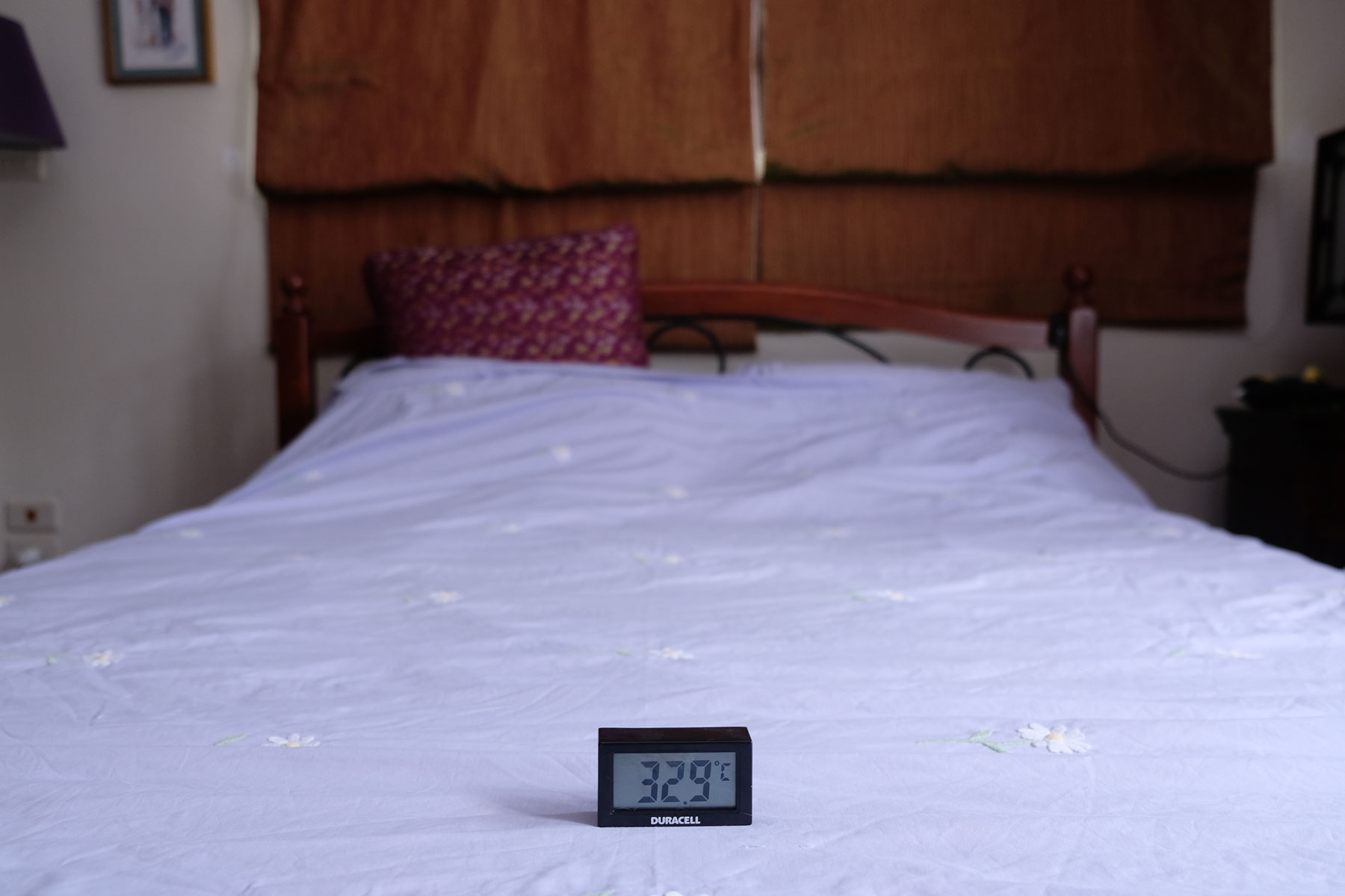 Ein Bett, auf dem ein Thermometer steht, das 32,9 °Celsius anzeigt.