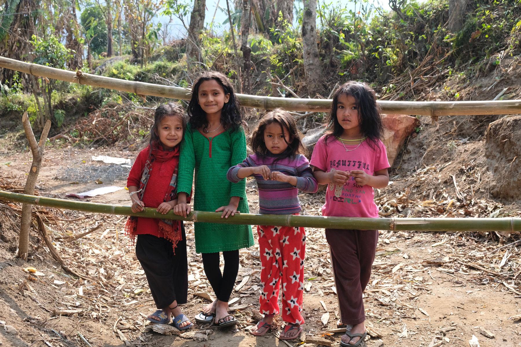 Vier nepalesische Mädchen stehen an einem Holzzaun.