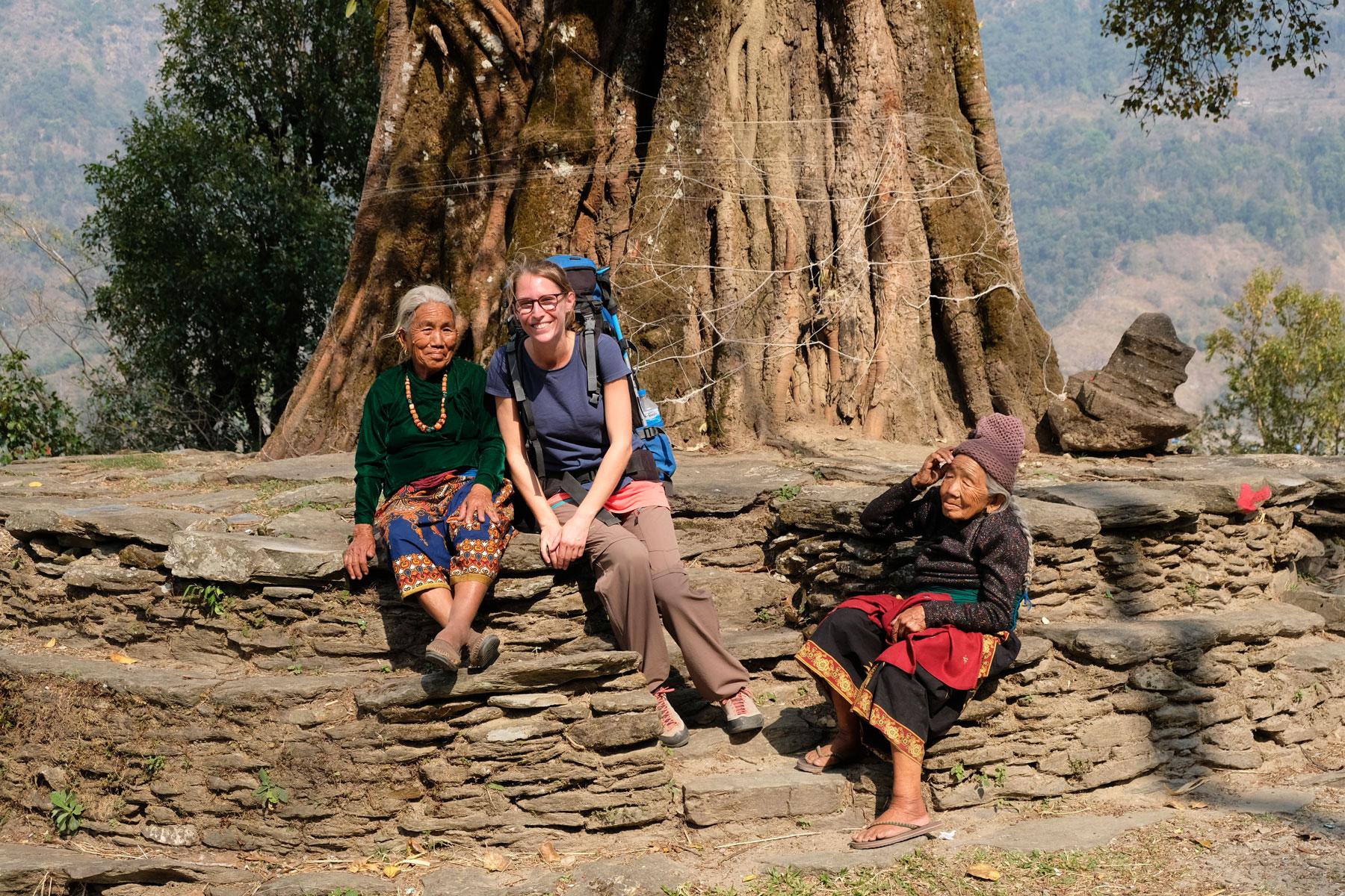 Leo sitzt neben zwei alten nepalesischen Frauen auf einer Steinmauer.