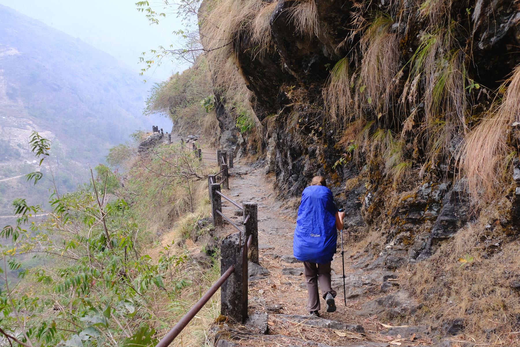 Leo wandert mit Rucksack und Regenschutz auf einem Wanderweg.