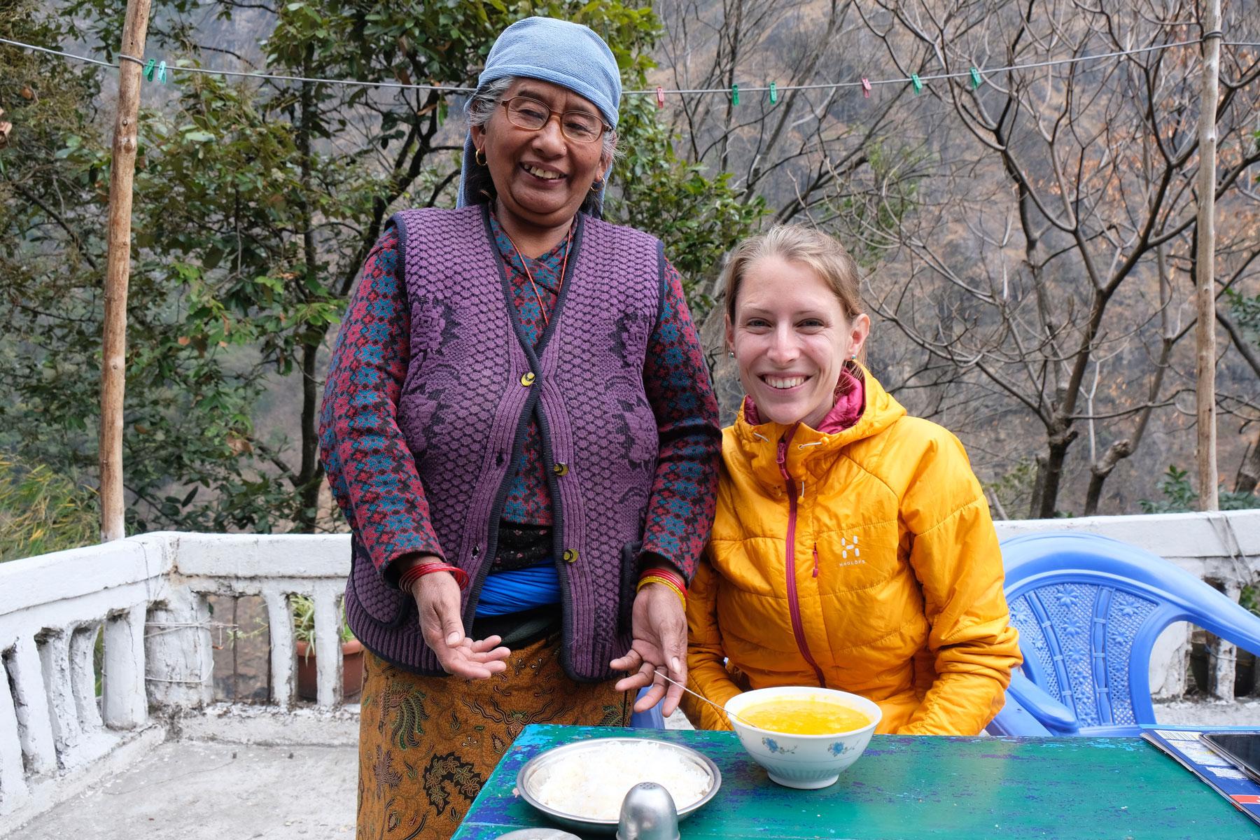 Leo sitzt an einem Tisch. Neben ihr steht eine nepalesische Frau.