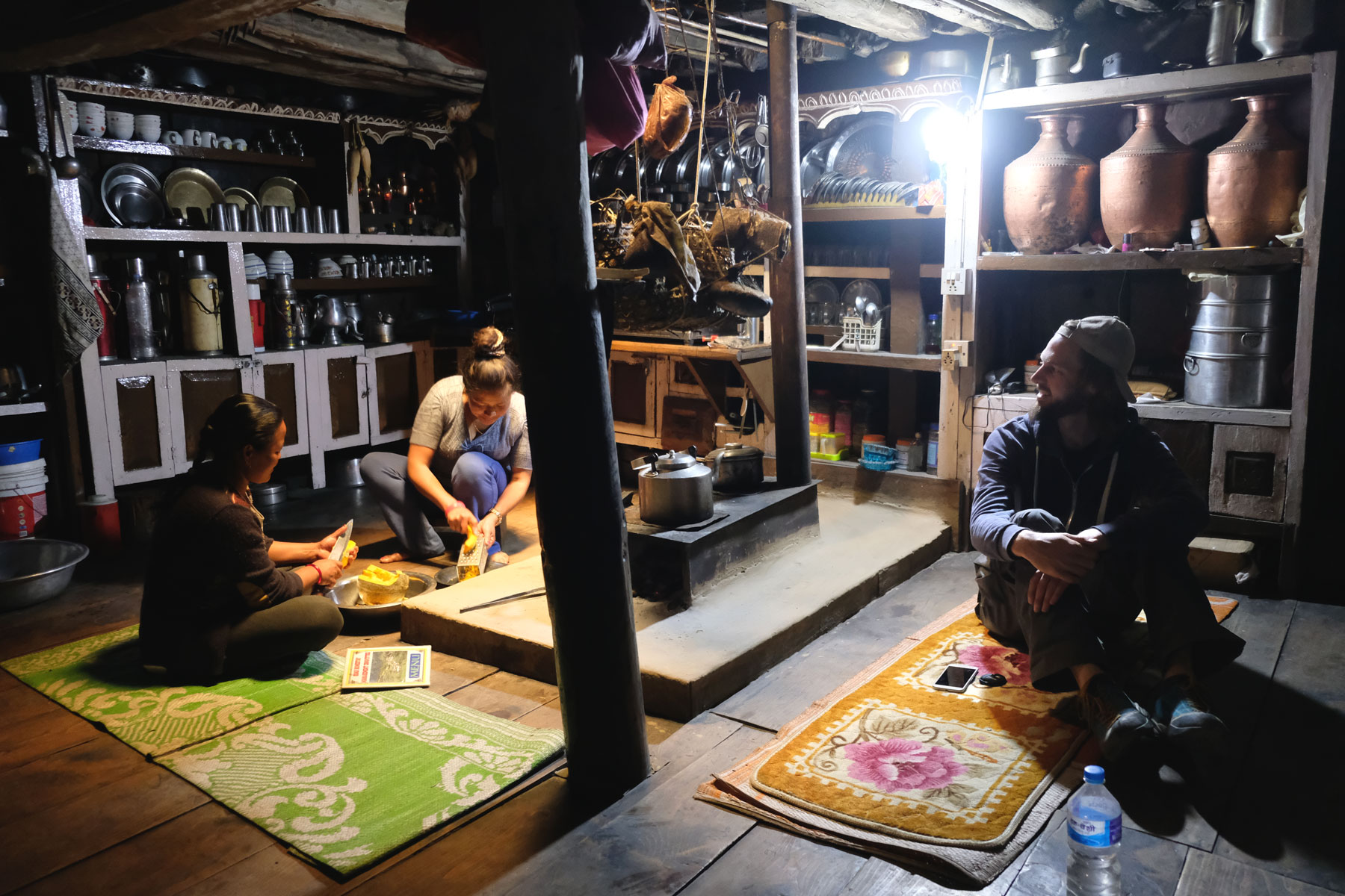 Sebastian sitzt mit zwei Frauen in einem traditionellen Haus in Odar auf dem Annapurna Circuit.