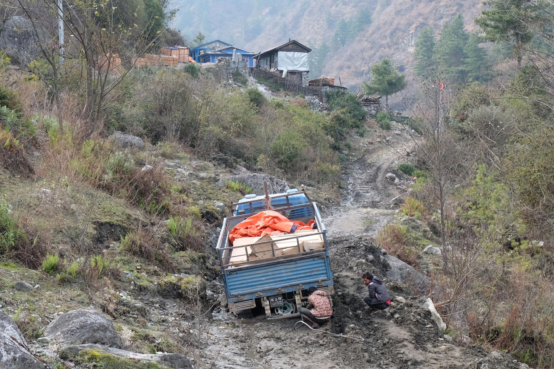 Ein Lastwagen, der auf einer schlammigen Straße feststeckt.