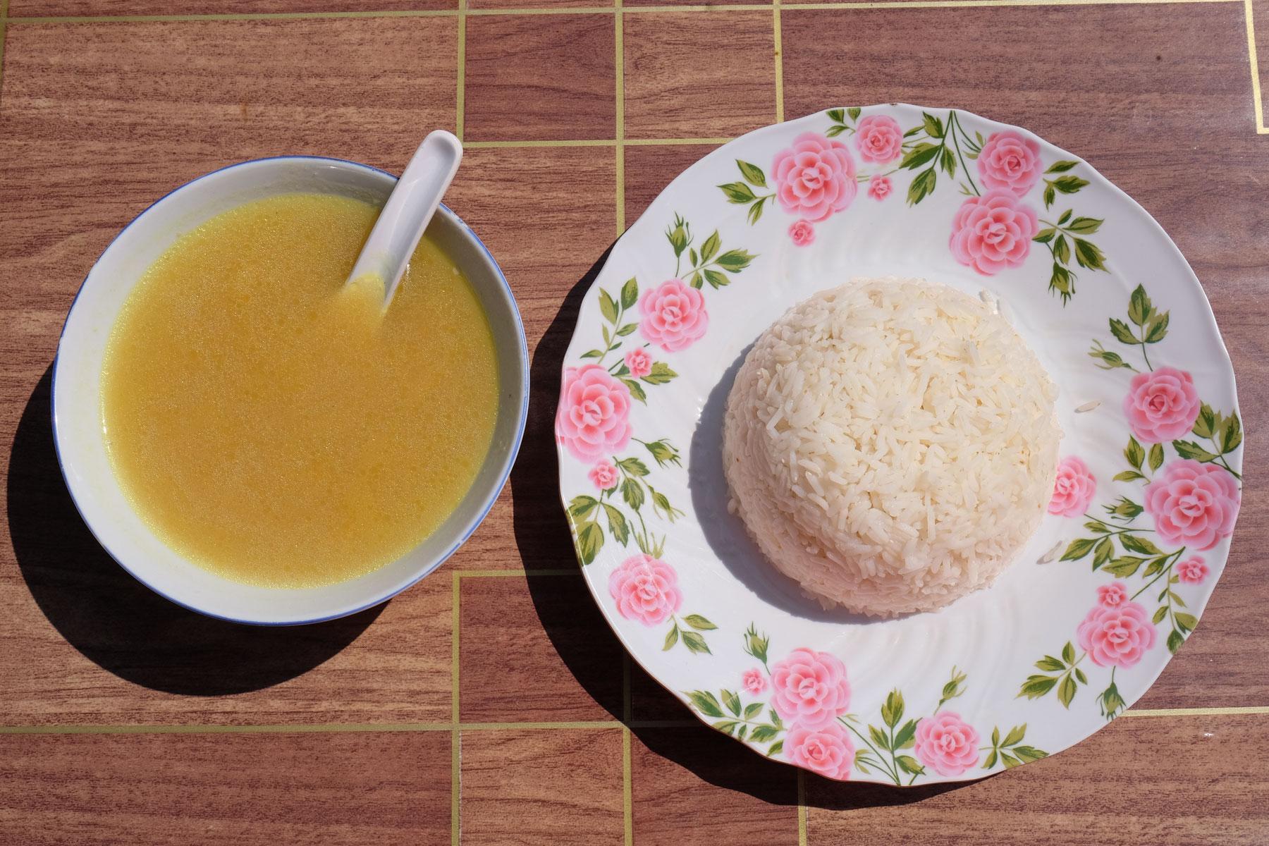Eine Schale mit Kürbissuppe und ein Teller voll Reis.