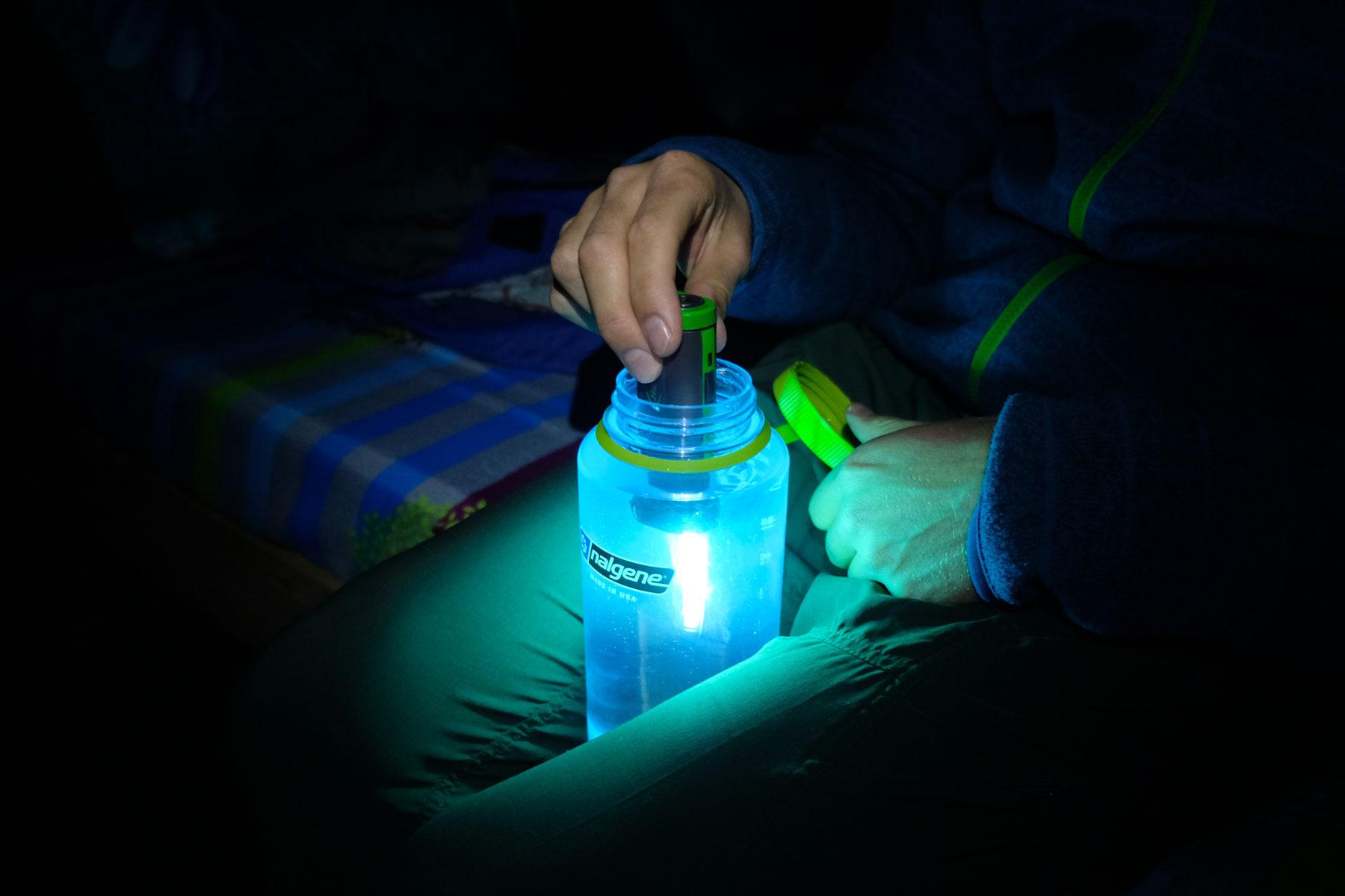Eine Hand bewegt einen Steripen, um Wasser in einer Flasche zu entkeimen.
