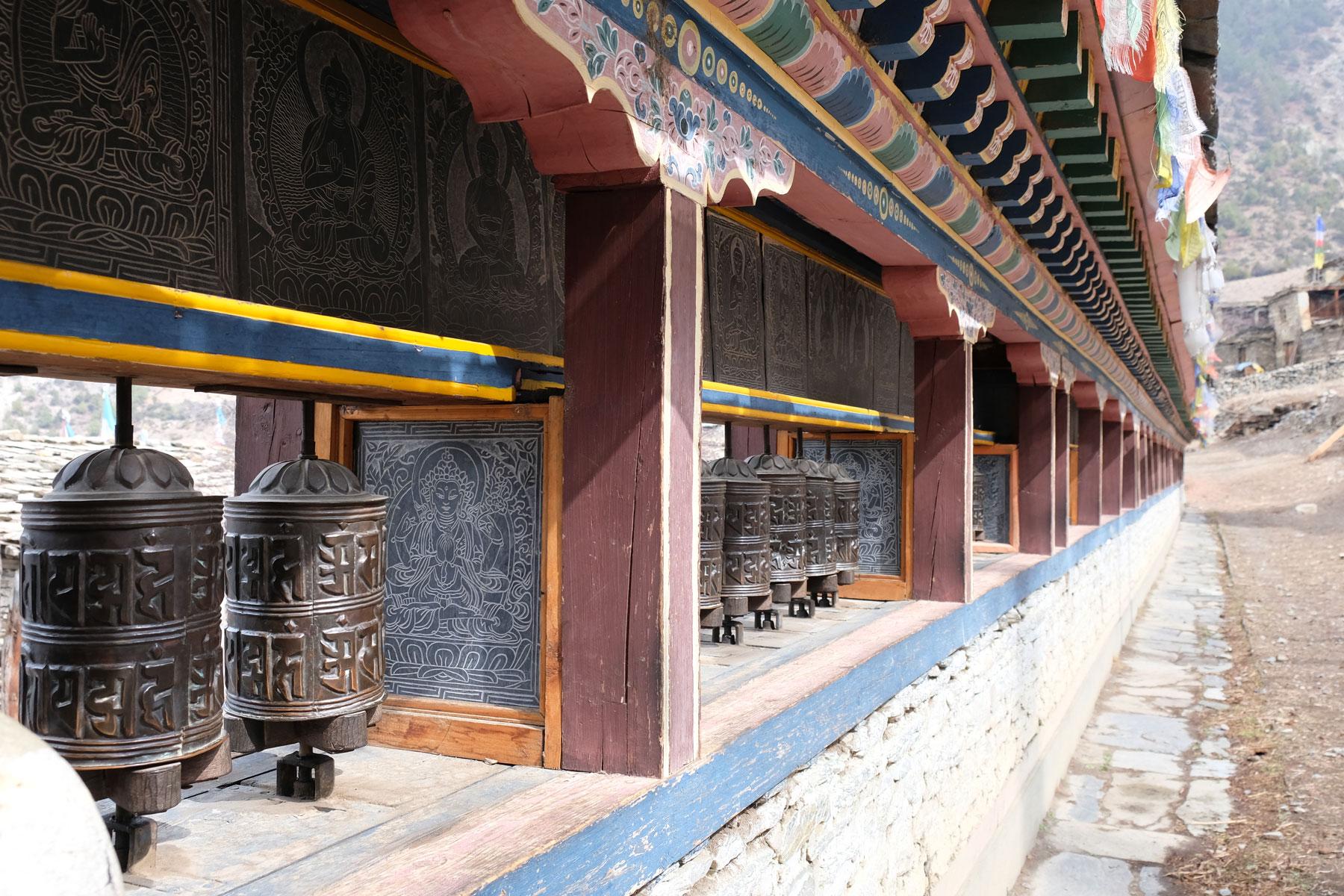 Eine Wand mit buddhistischen Gebetsmühlen.