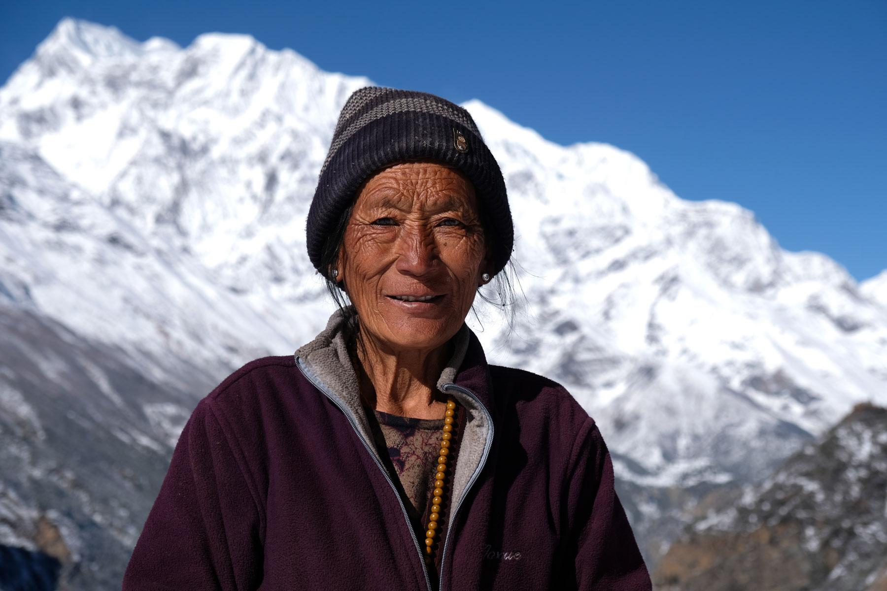 Eine alte nepalesische Frau vor schneebedeckten Bergen.