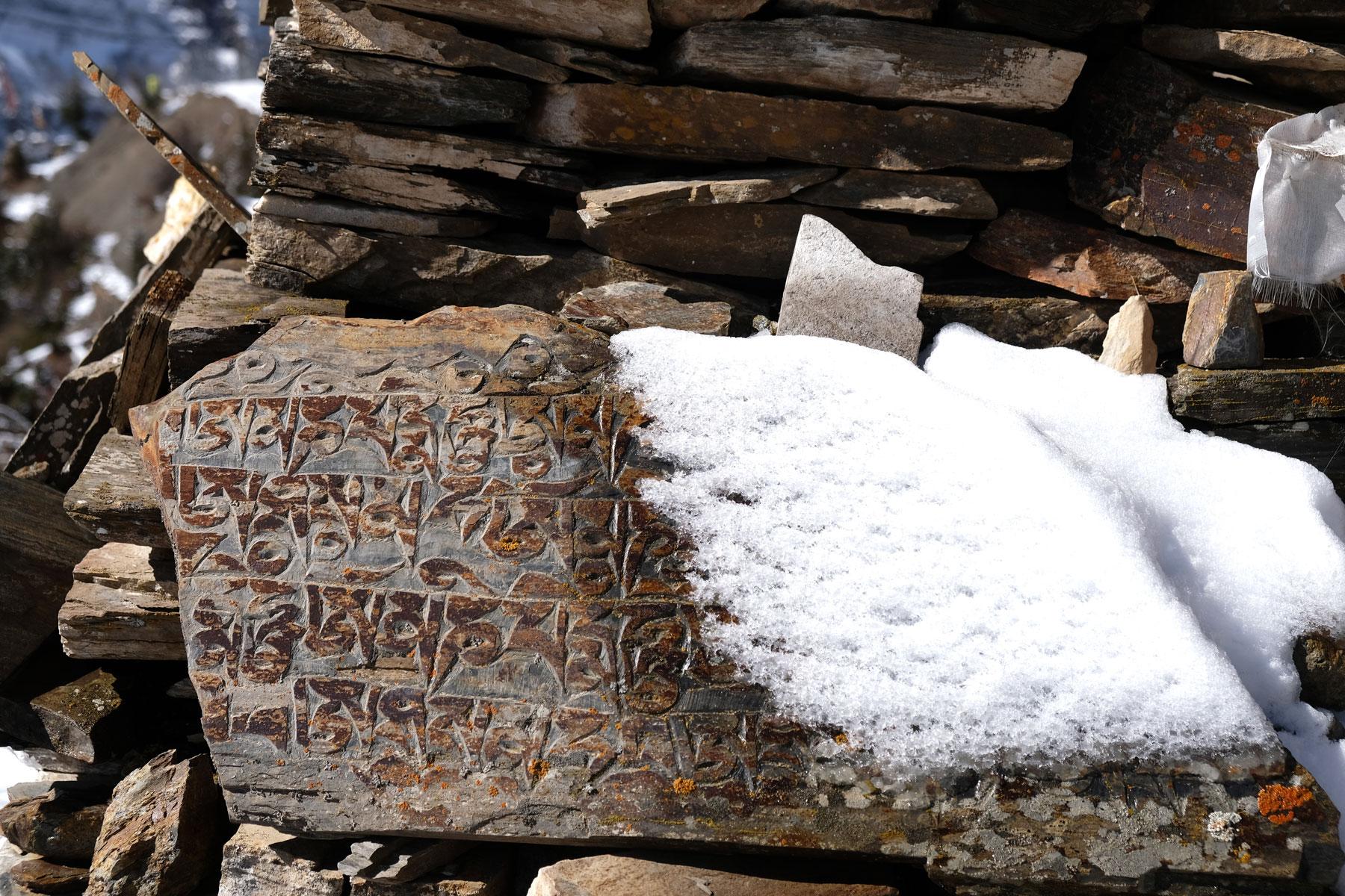 Tibetische Schriftzeichen auf einer schneebedeckten Steintafel.