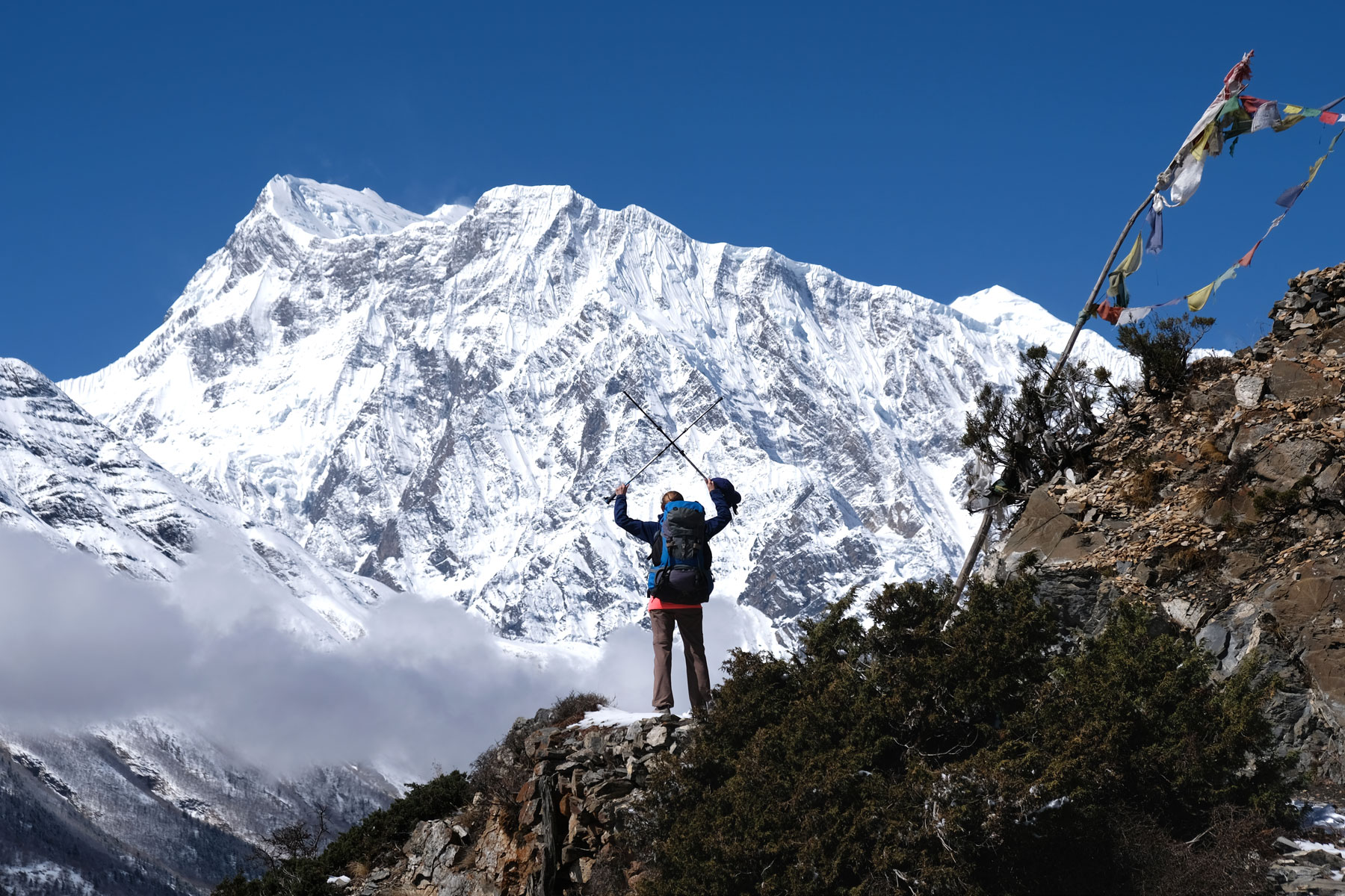 Leo streckt vor einem schneebedeckten Berg im Annapurnagebirge Wandersöcke in die Höhe.