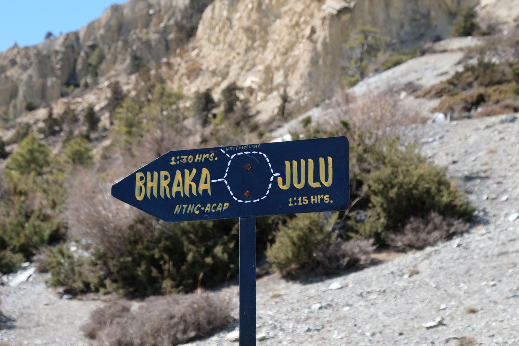 Ein Wegweise auf dem Annapurna Circuit, auf dem der Weg nach Bhraka und Julu beschrieben wird.
