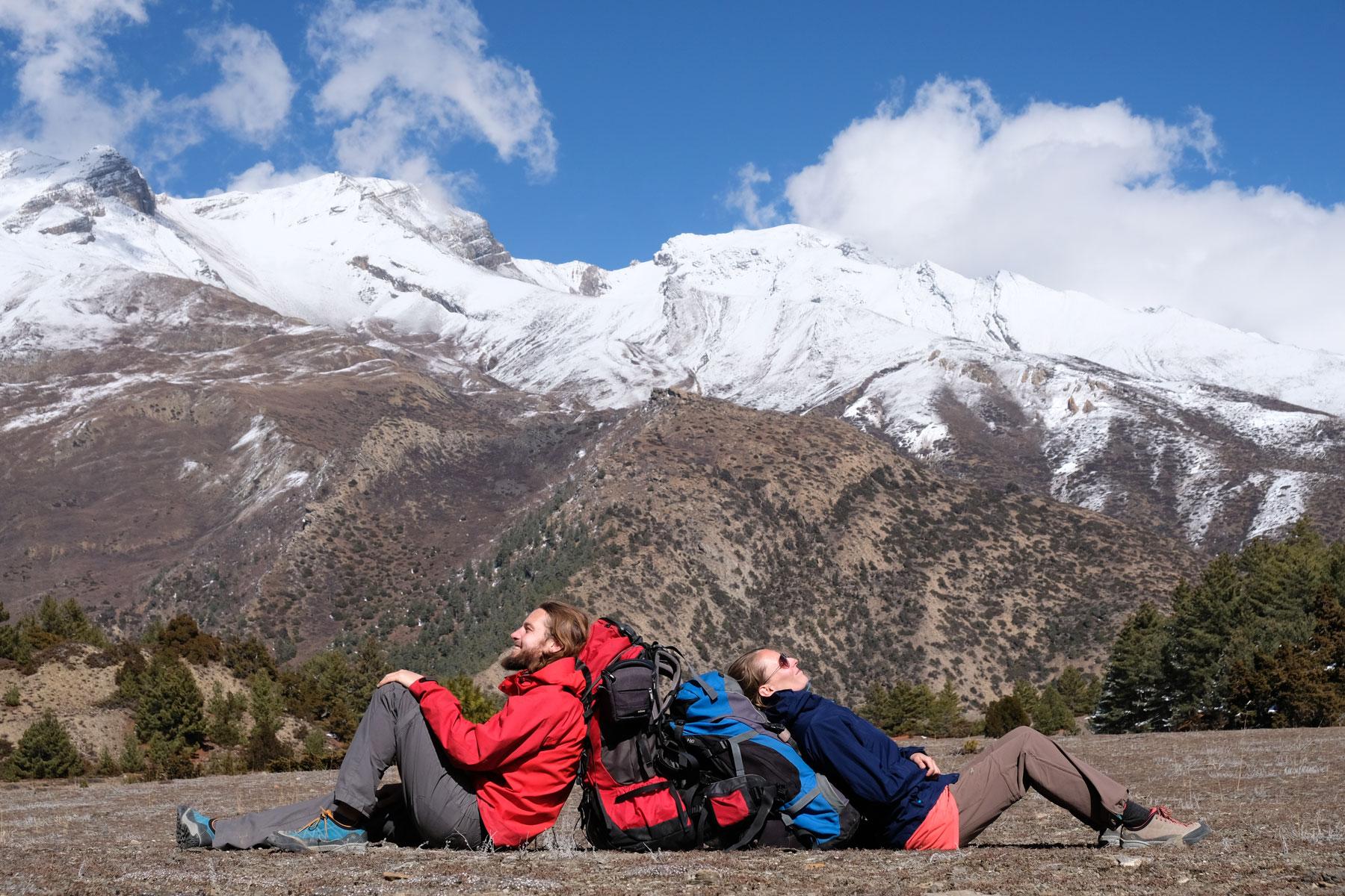 Sebastian und Leo sitzen an ihre Rucksäcke gelehnt vor Bergen im Annapurnagebirge.