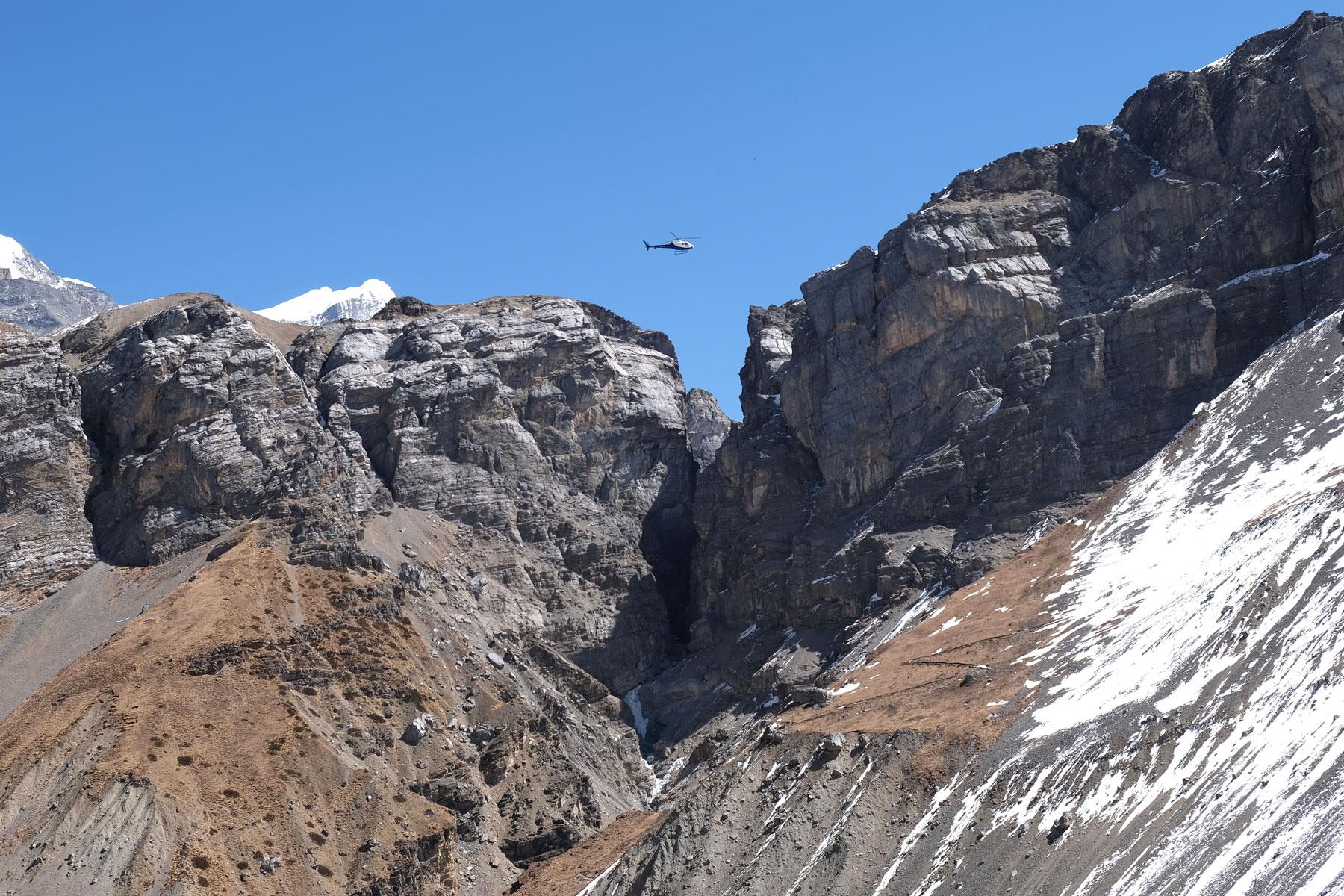 Ein Hubschrauber fliegt über den Bergen des Annapurna Circuit.