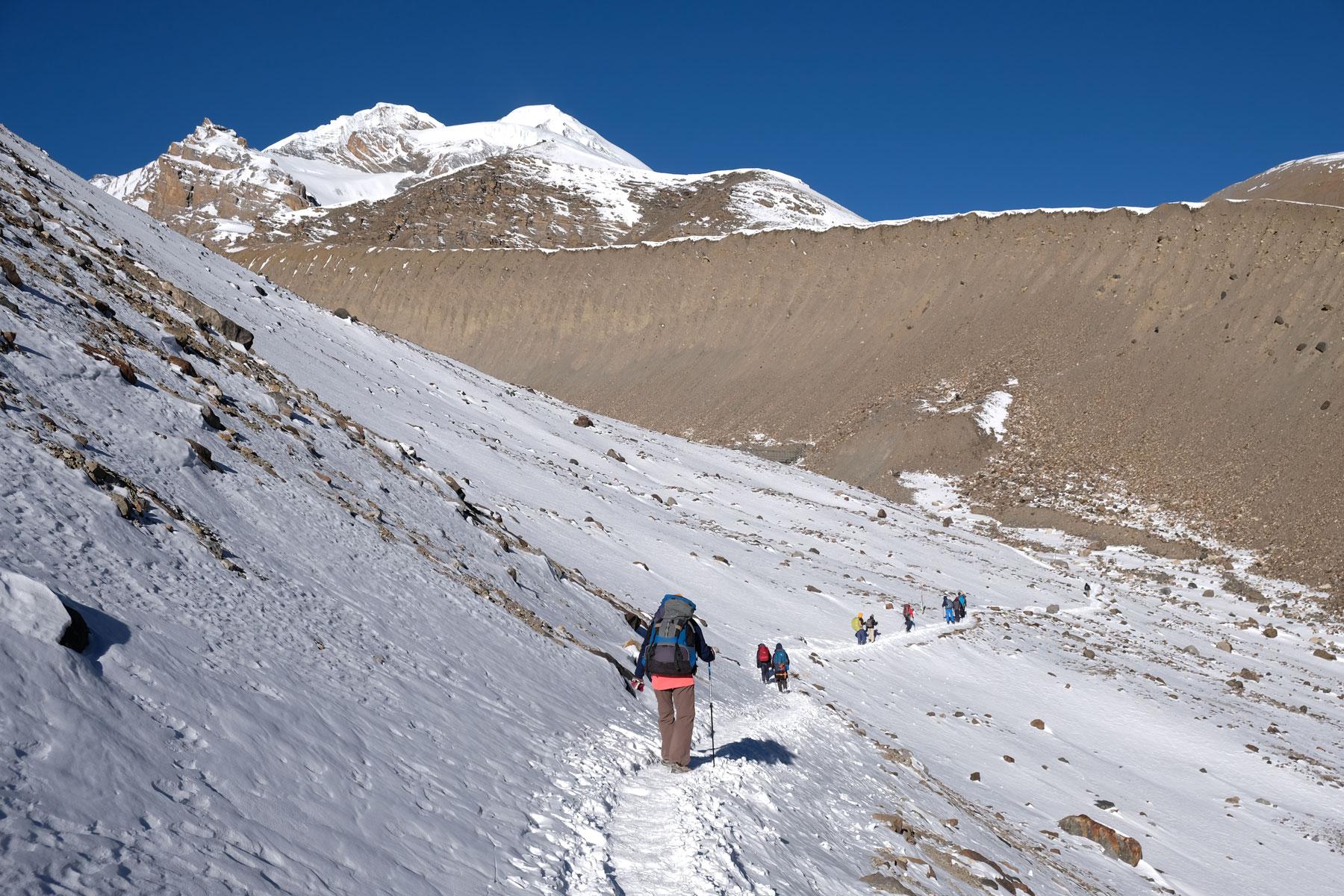 Leo und andere Wanderer auf einem schneebedeckten Pfad auf dem Annapurna Circuit.
