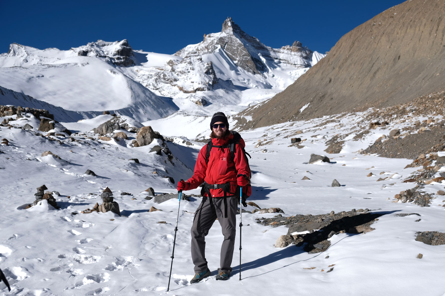 Sebastian mit Wanderstöcken auf schneebedeckten Bergen des Annapurna Circuit.
