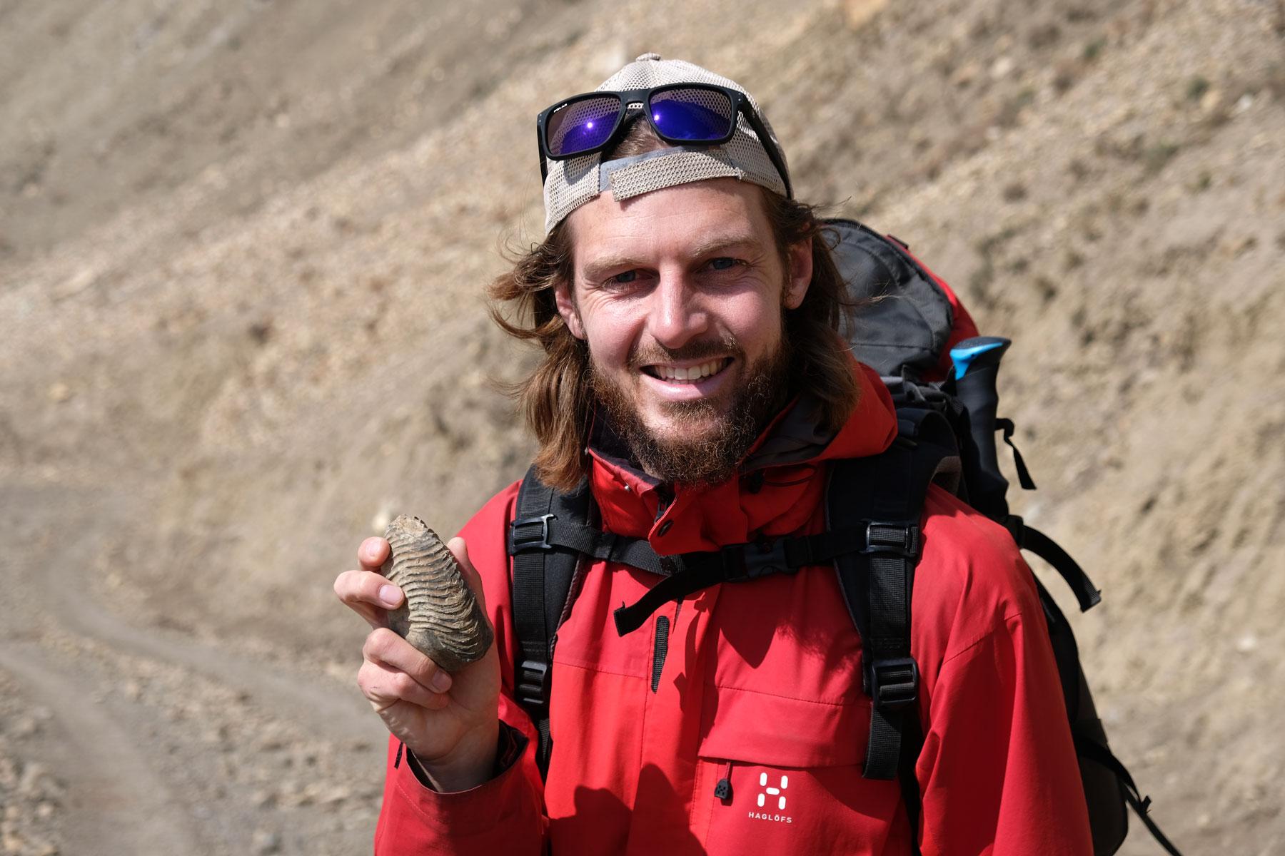 Sebastian hält ein Fossil in der Hand.