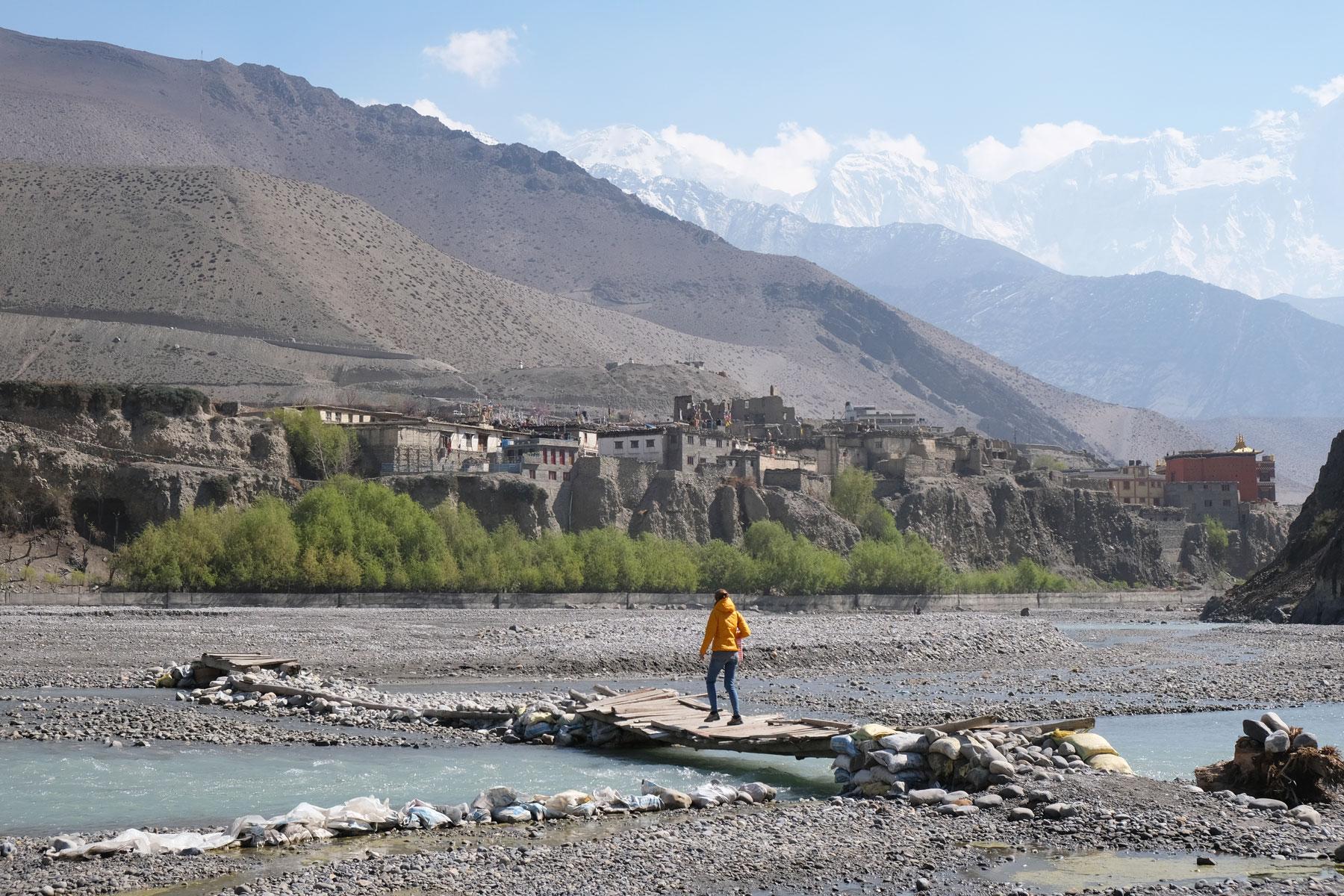 Leo geht im Flussbett des Kali Gandaki über eine schmale Holzbrücke.