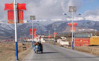 Eine mit chinesischen Flaggen gesäumte Straße in Tibet.
