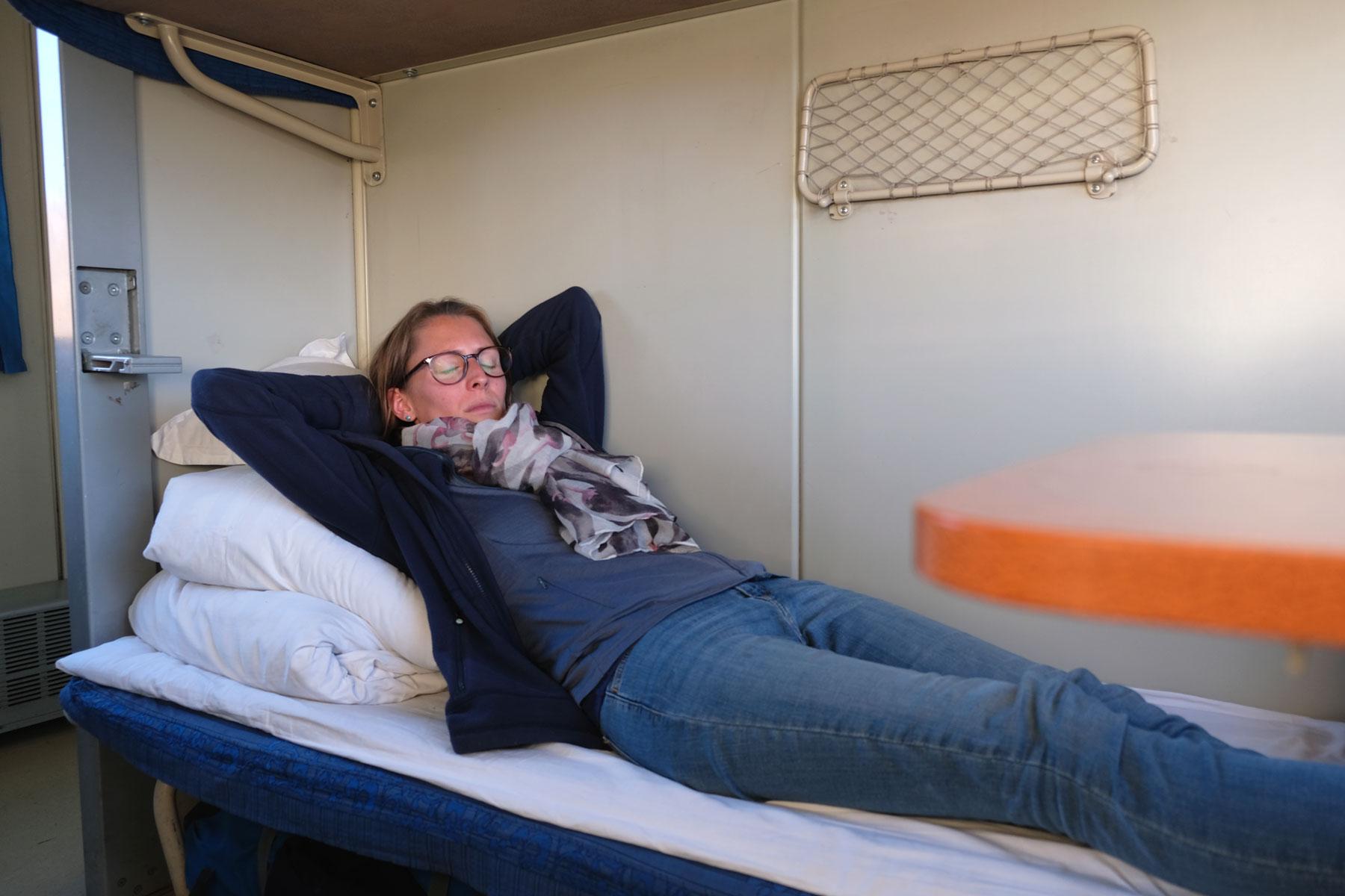 Leo schläft auf einem Bett im Zug von Lhasa nach Chengdu.