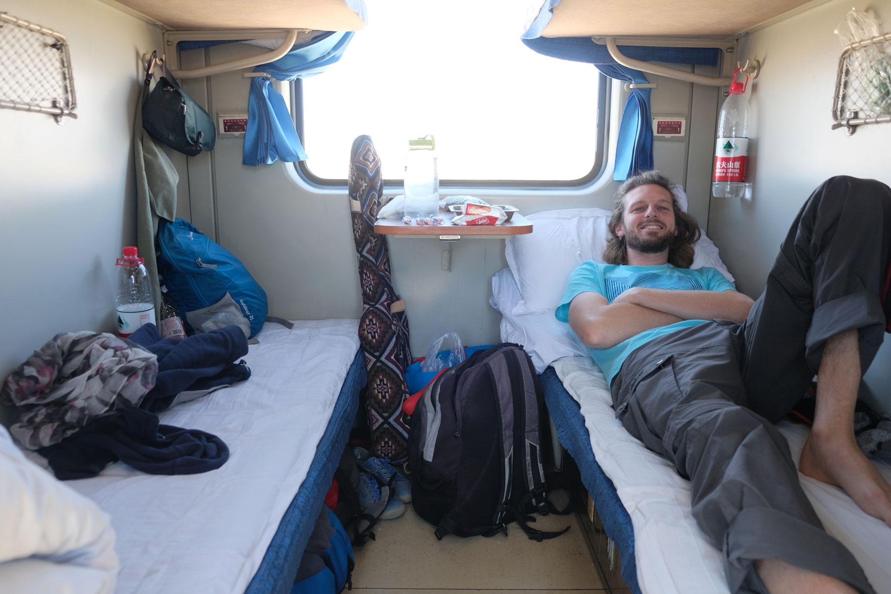 Sebastian liegt im Nachtzug von Lhasa nach Chengdu auf einem Bett.