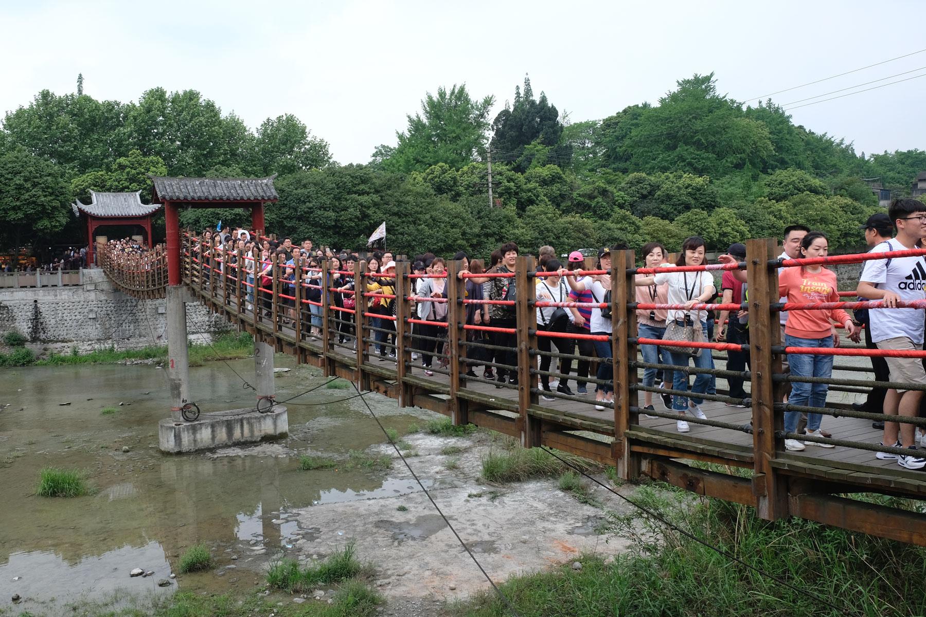 Chinesische Menschen gehen beim Bewässerungssystem von Dujiangyan über eine Hängebrücke.