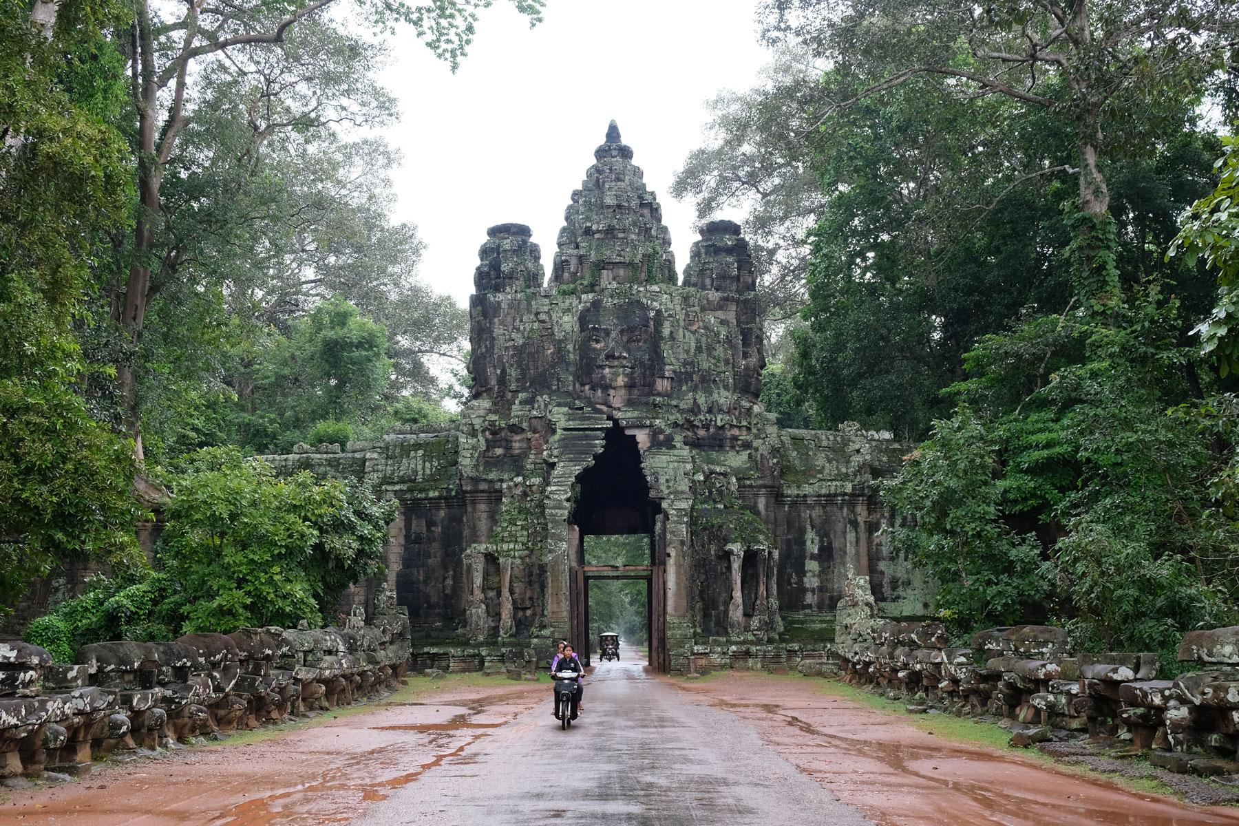 Ein Motorrad fährt durch das Victory Gate von Angkor Wat.