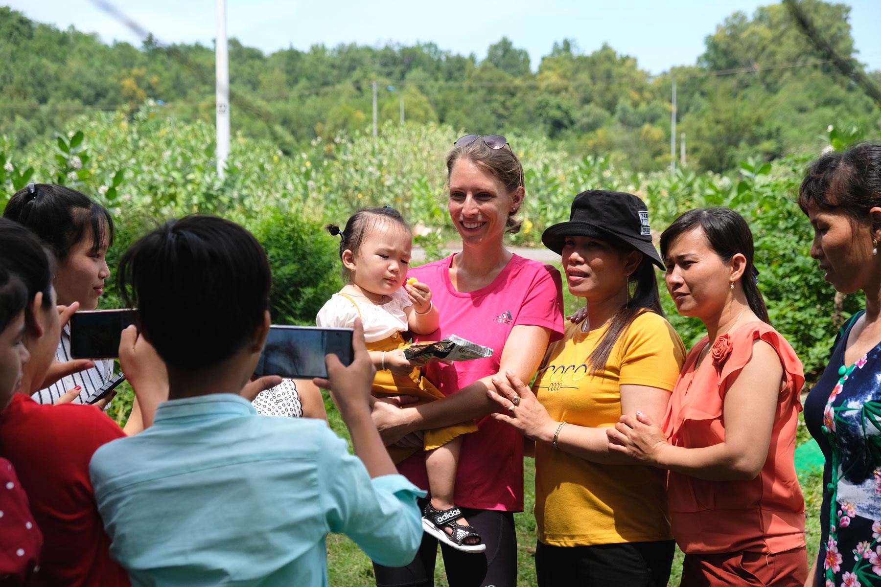 Leo hält ein Mädchen auf dem Arm und wir zusammen mit einer vietnamesischen Familie fotografiert.