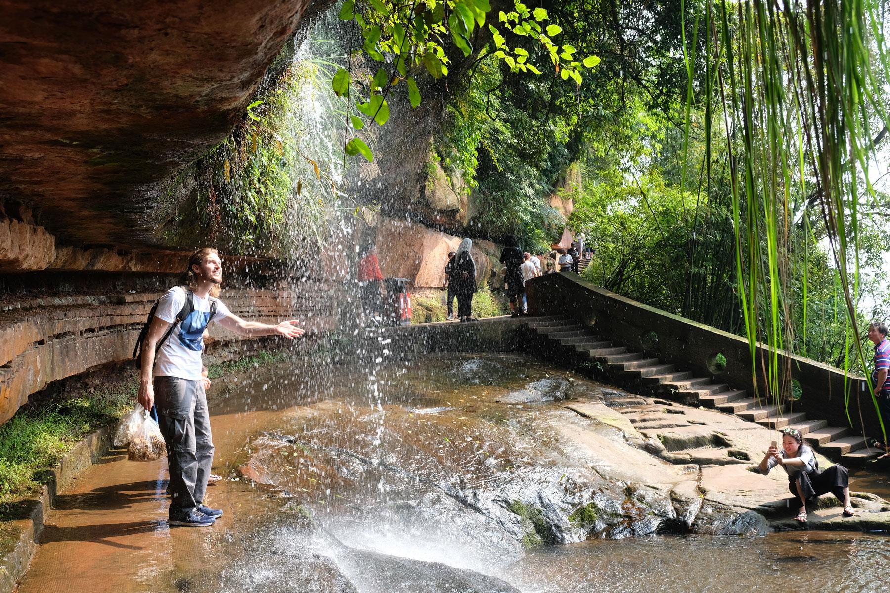Sebastian hält seine Hand in einen kleinen Wasserfall im Shunan Zhuhai Nationalpark.
